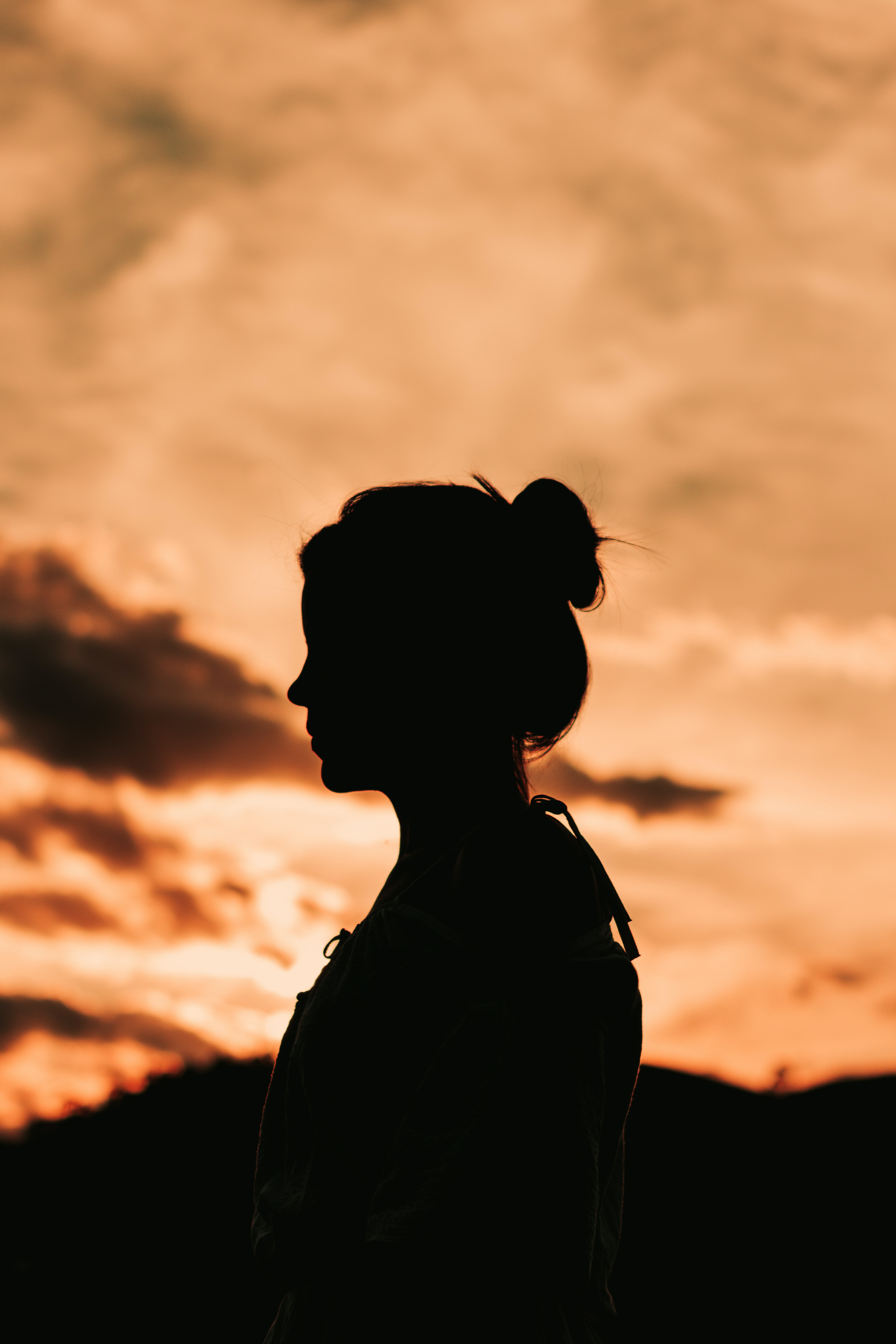 Silhouette of a woman standing alone under an orangesunset