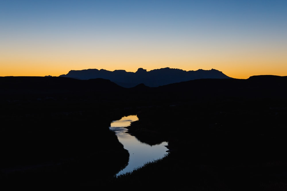 landscape photography of river leading to mountain
