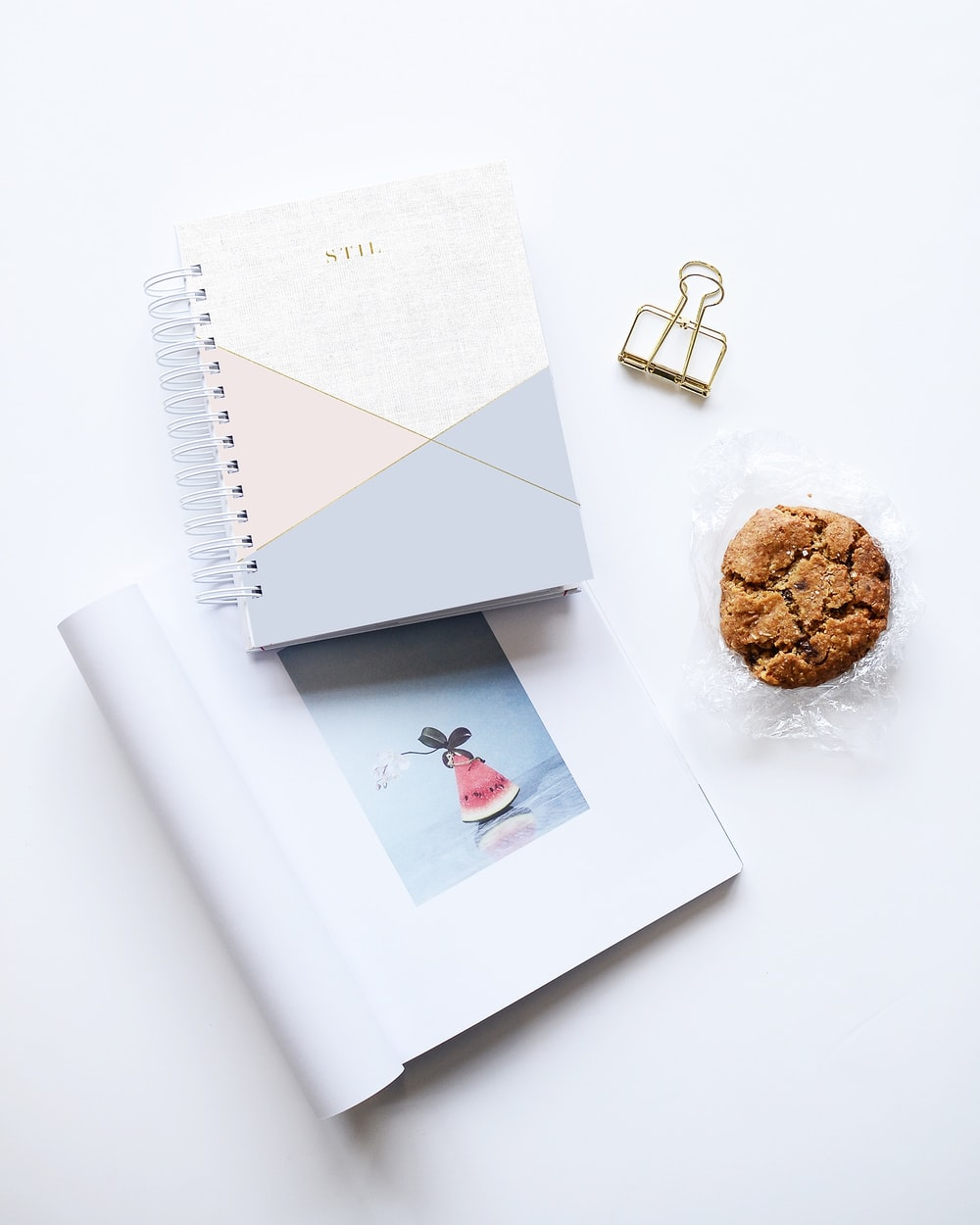 cookie beside two notebooks on white surface