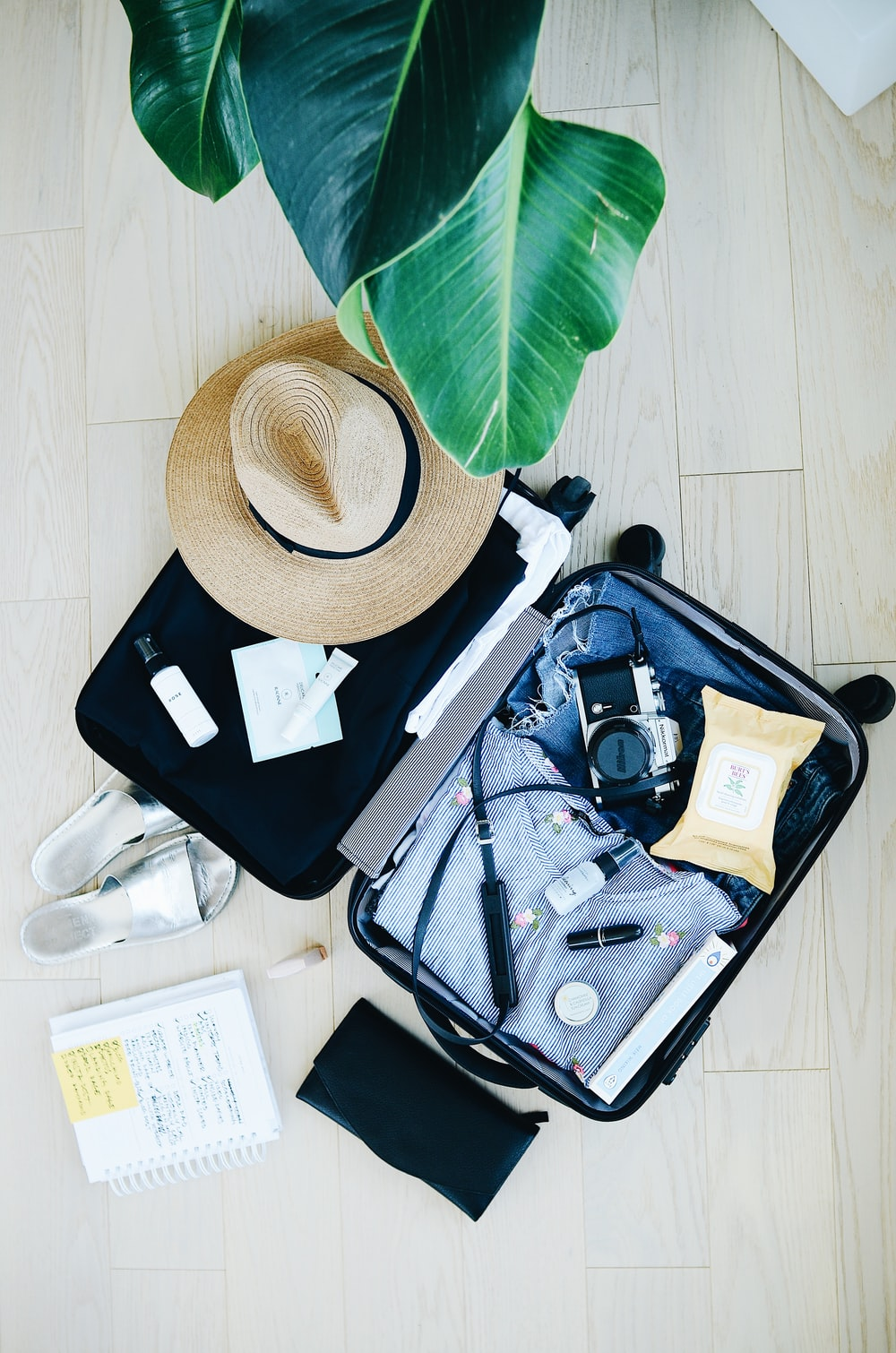 Photo Via: Unsplash.com, Flat lay of a packed vacation suitcase, STIL @stilclassics.