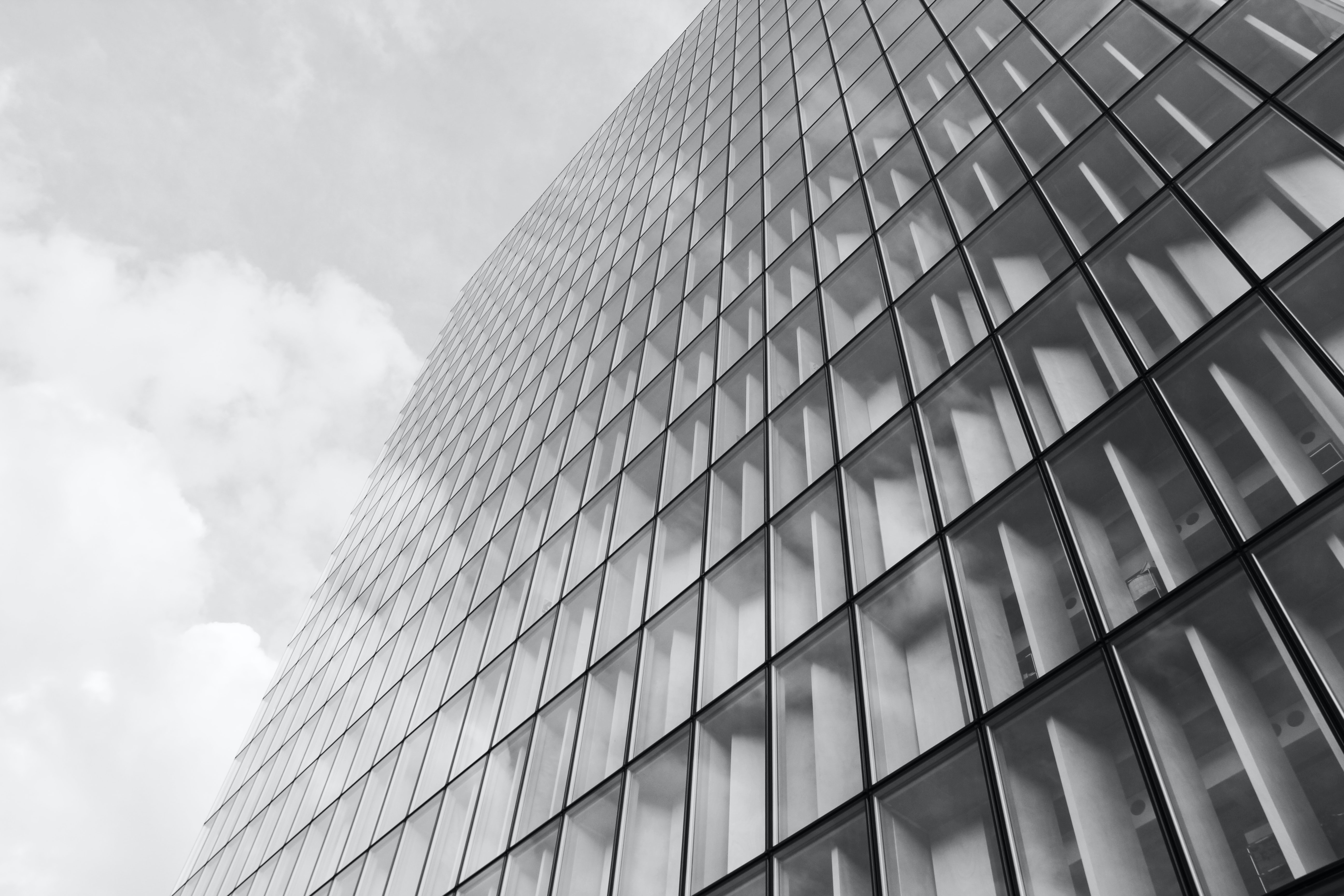 Black and white photo of skyscraper with thin black lines under cloudy sky