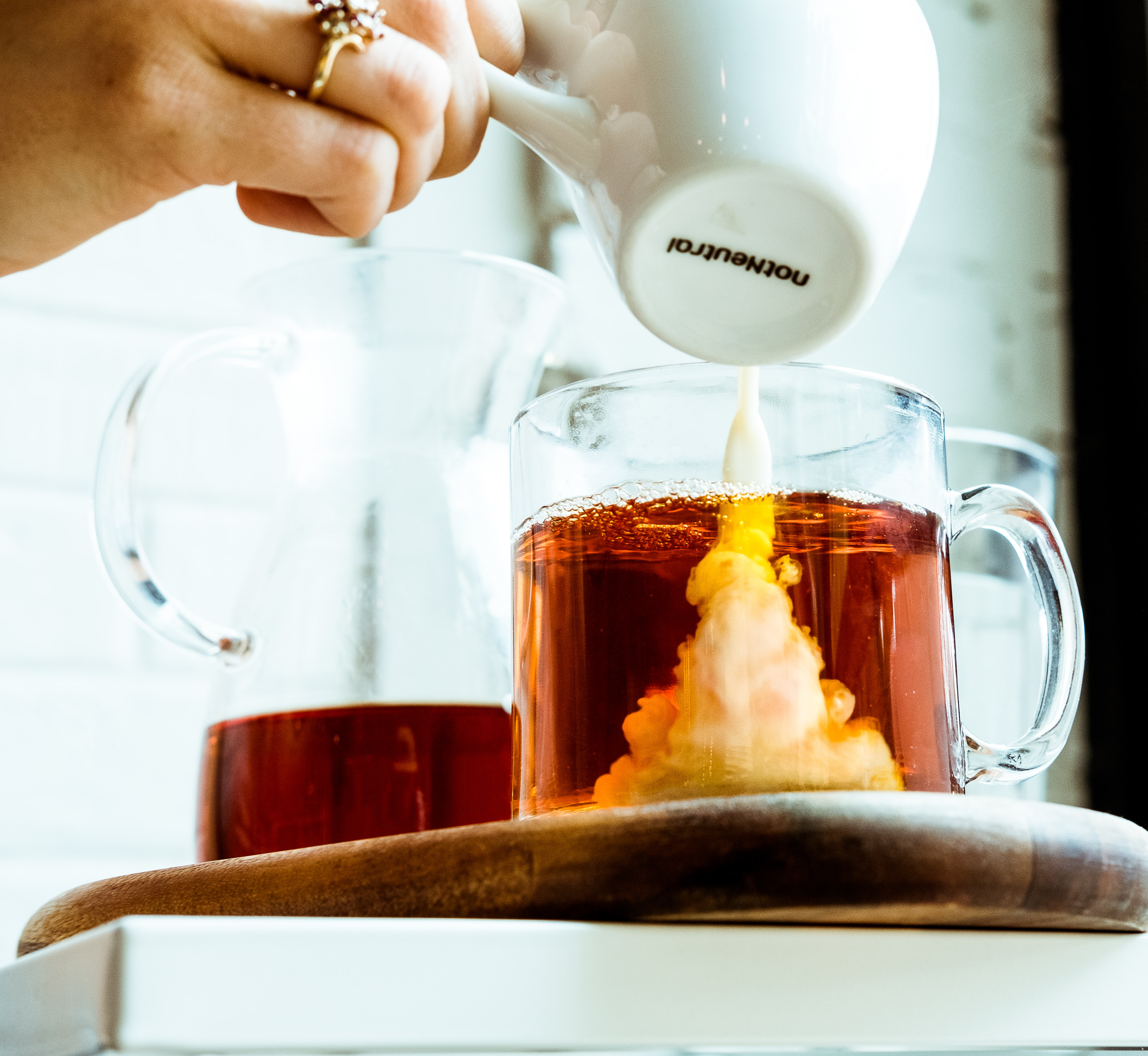 person pouring milk in tea