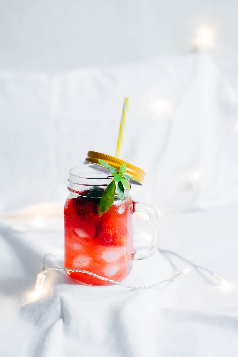 clear glass mason mug with strawberry drink on white textile surrounded by string light