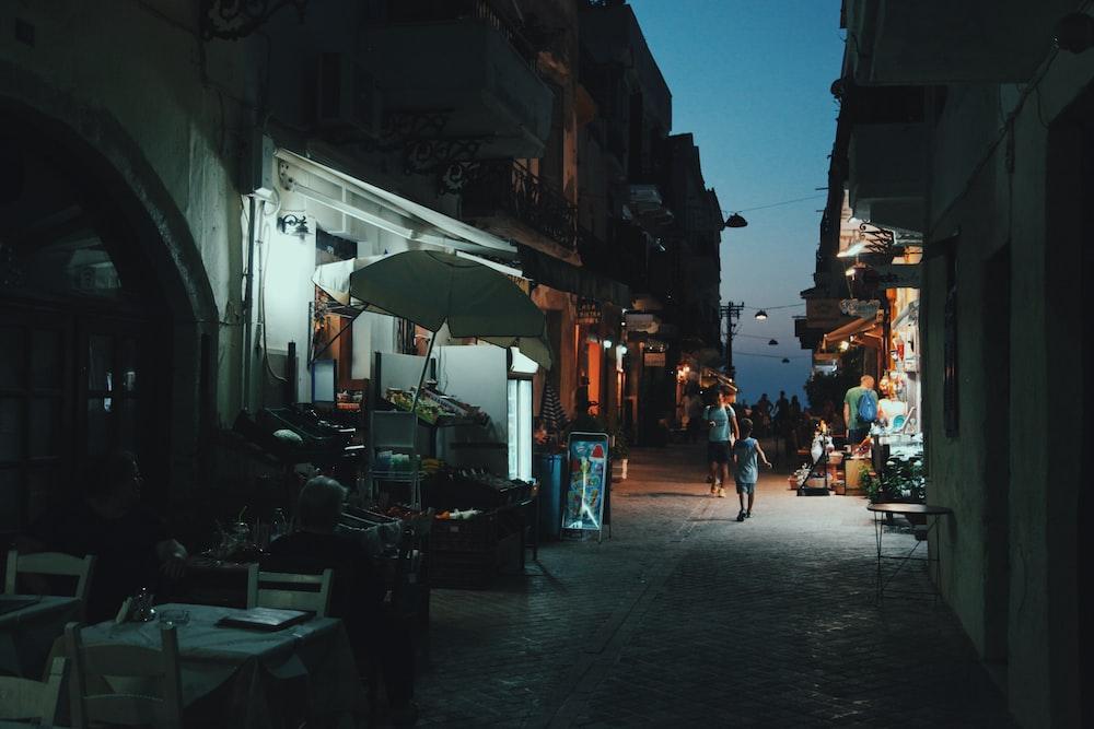 person walking near fruit lot at nighttime