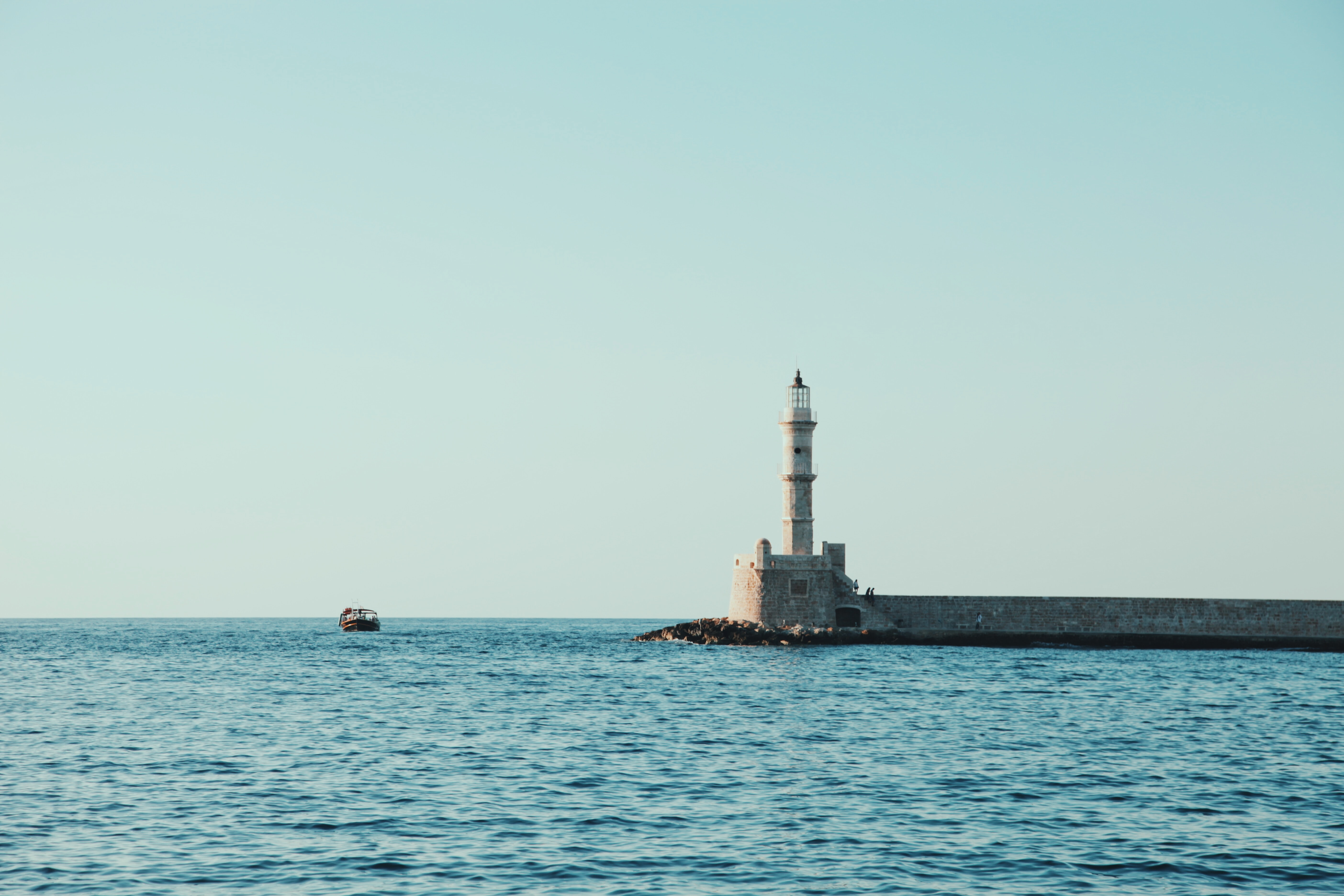 white and gray lighthouse surrounded by body of water under blue sky at daytime