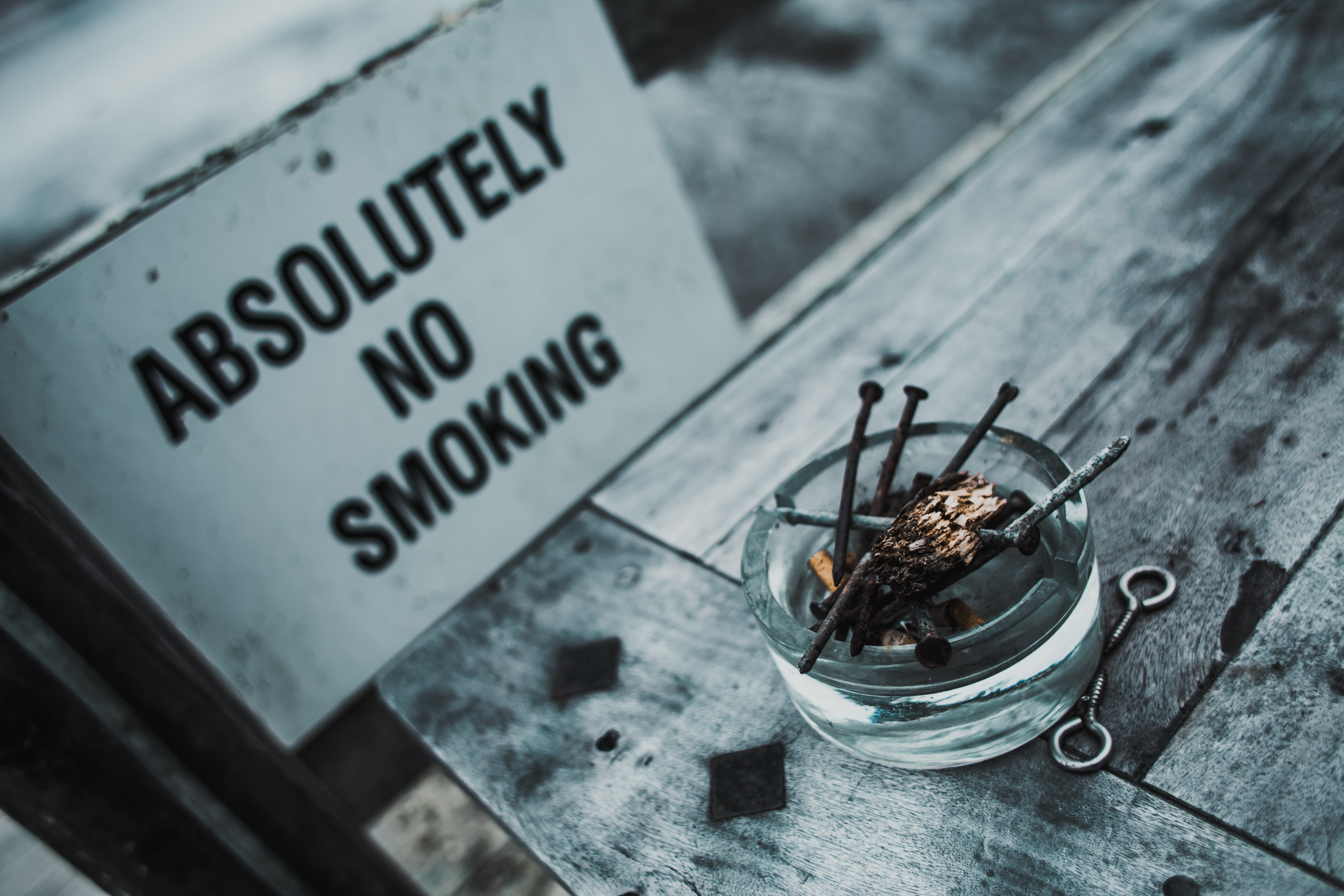 Ashtray with rusty nails by a No Smoking sign
