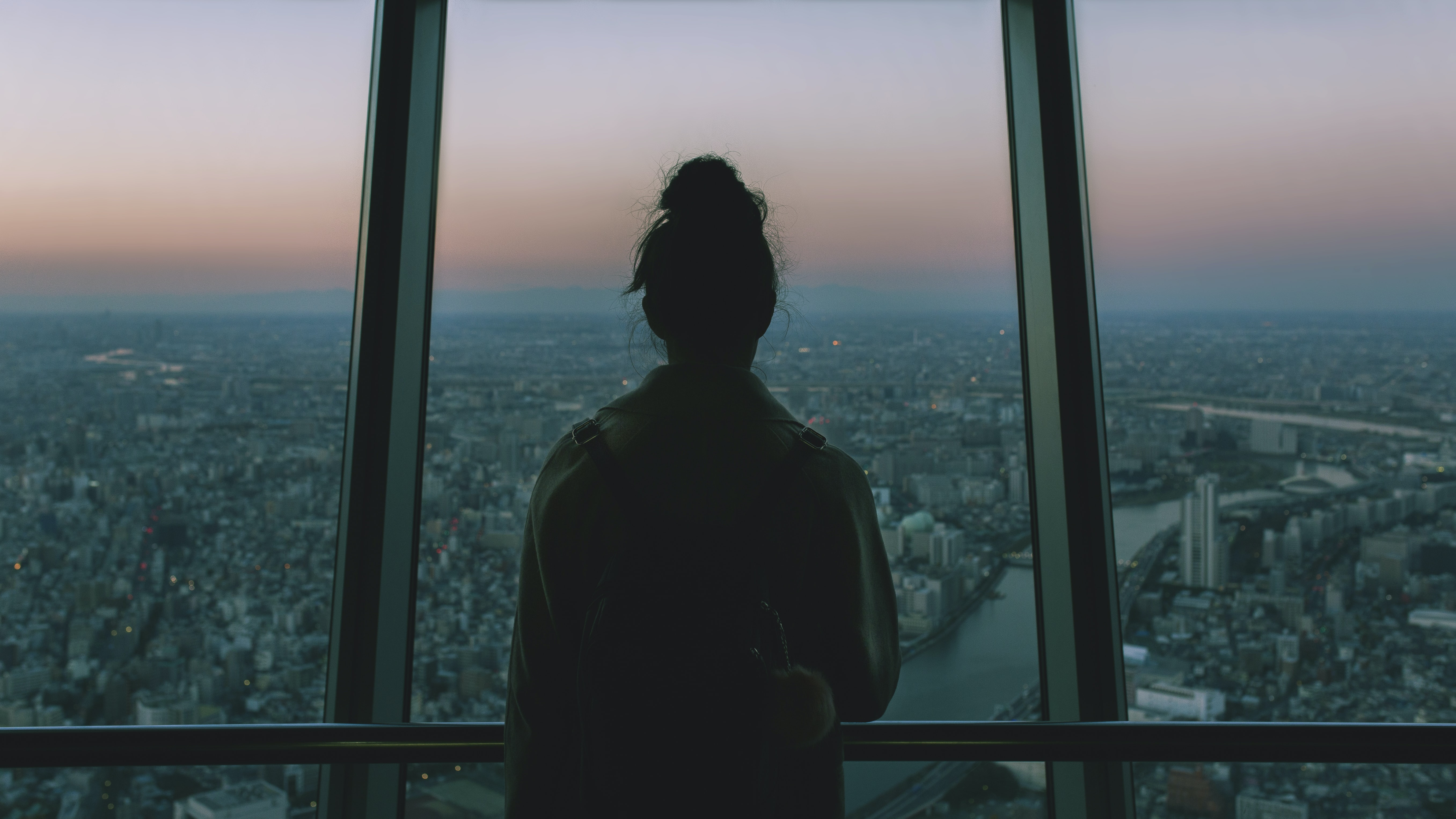 silhouette of person standing inside the building facing the glass mirror watching the city