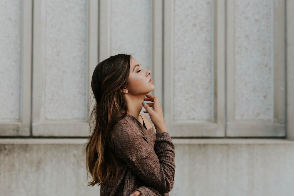 woman in brown long-sleeved top standing beside wall