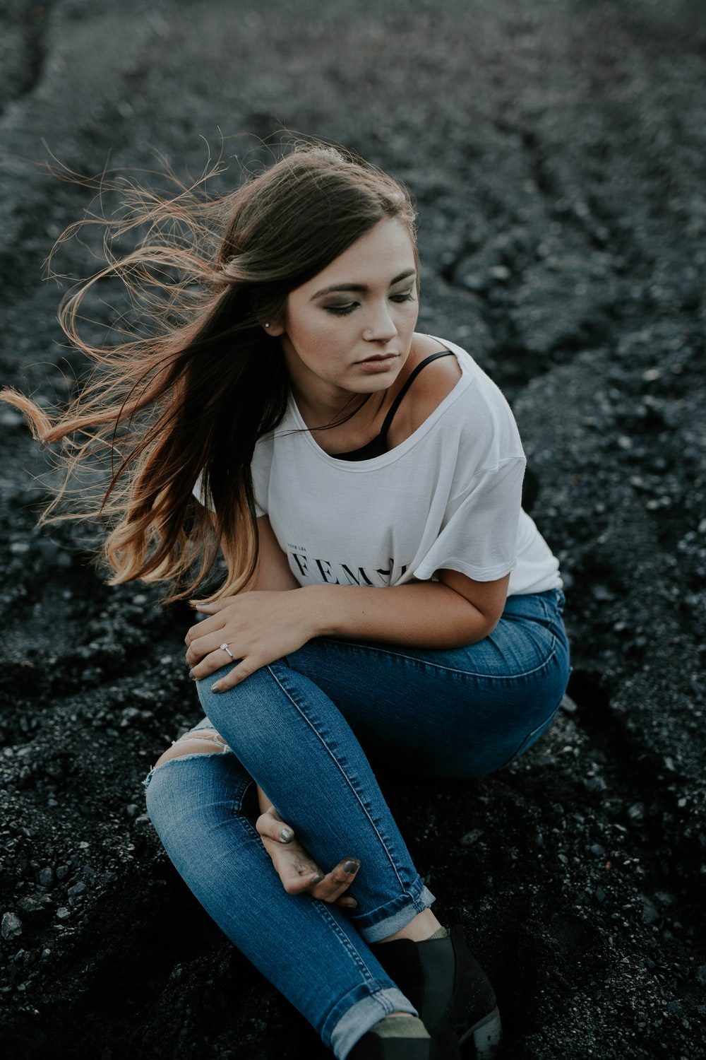 woman wearing scoop-neck shirt and distressed jeans sitting on ground while holding knee