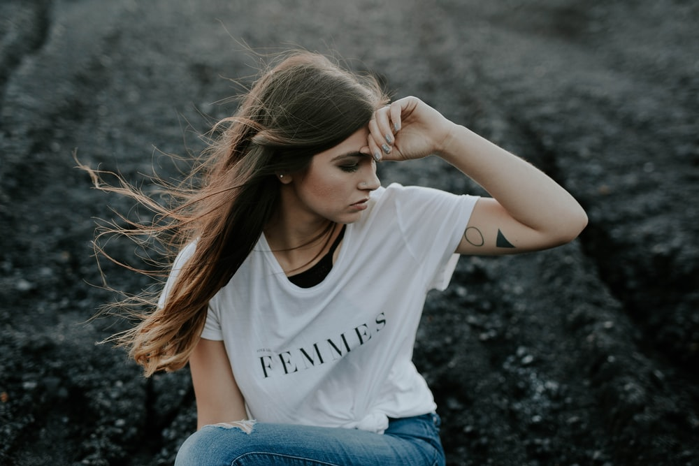 woman in white shirt sitting on ground
