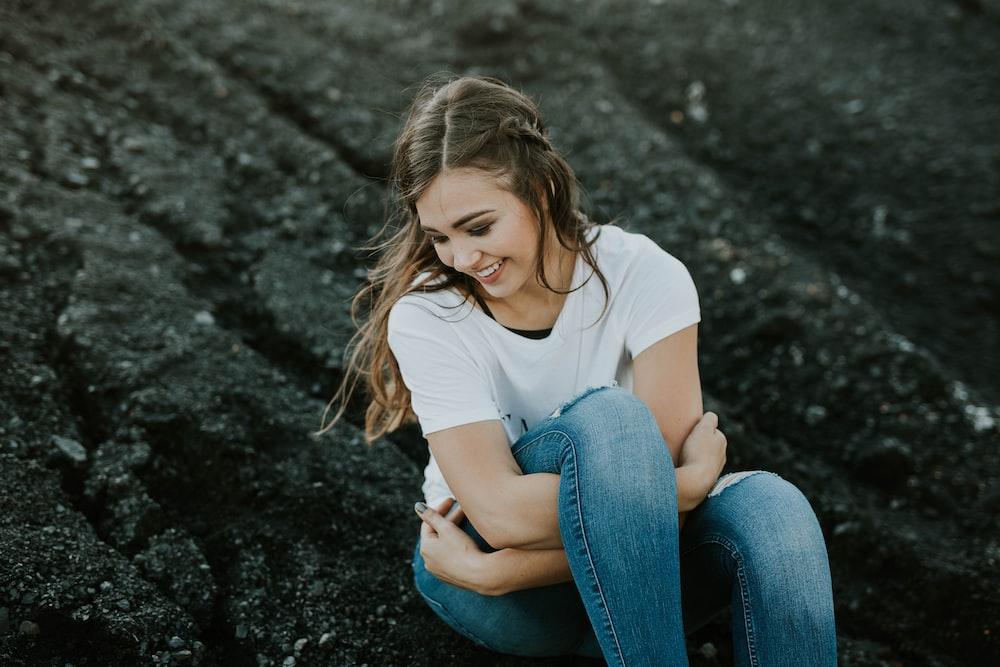 woman sitting on black soil during daytime