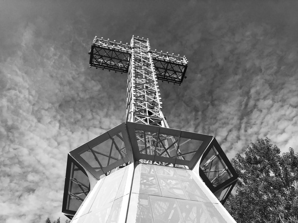 Black and white bottom view of a huge industrial metal cross framed by trees and clouds