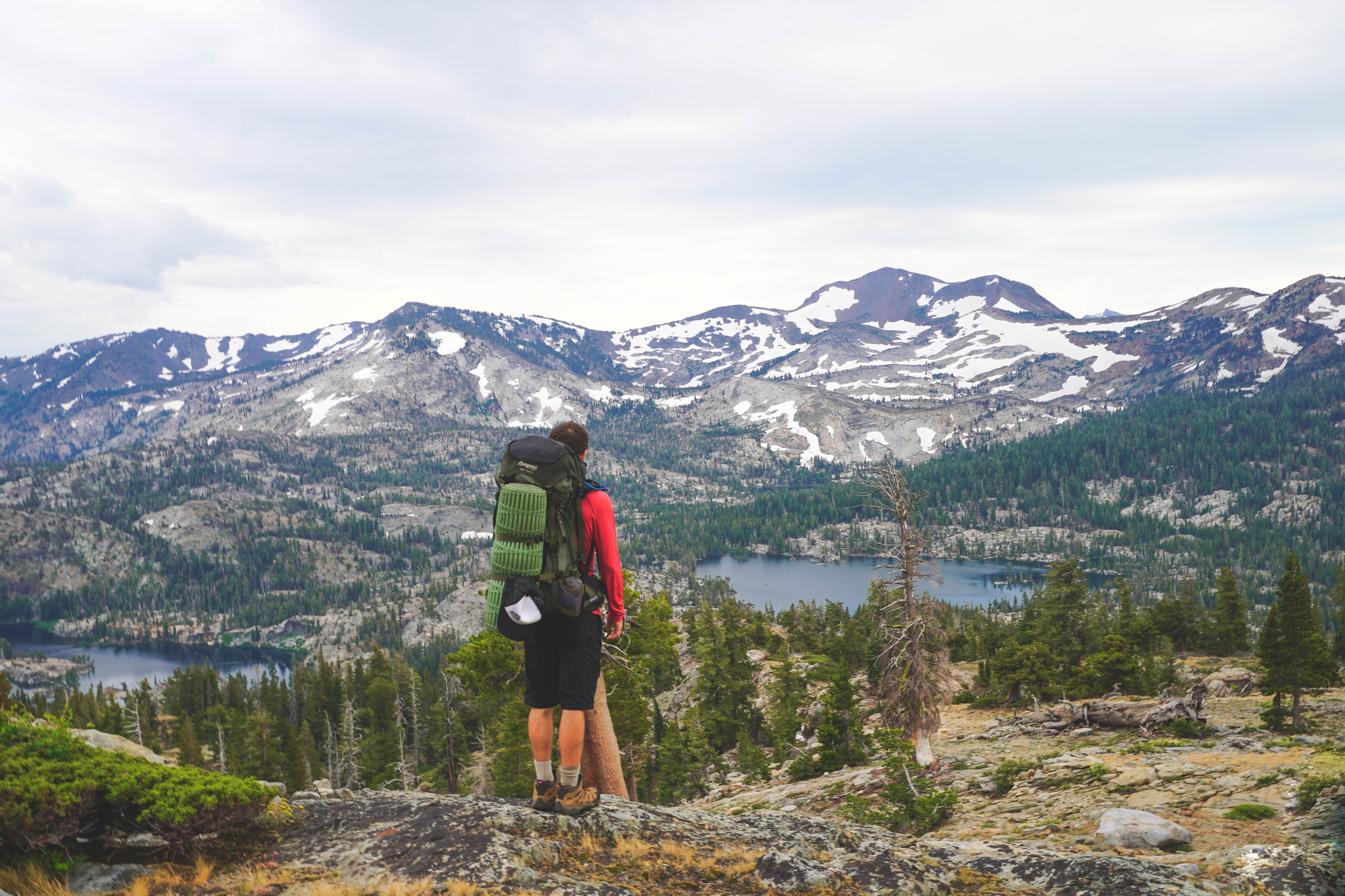 Backpacker looks out at sparse forests and snowy mountains in Desolation Wilderness