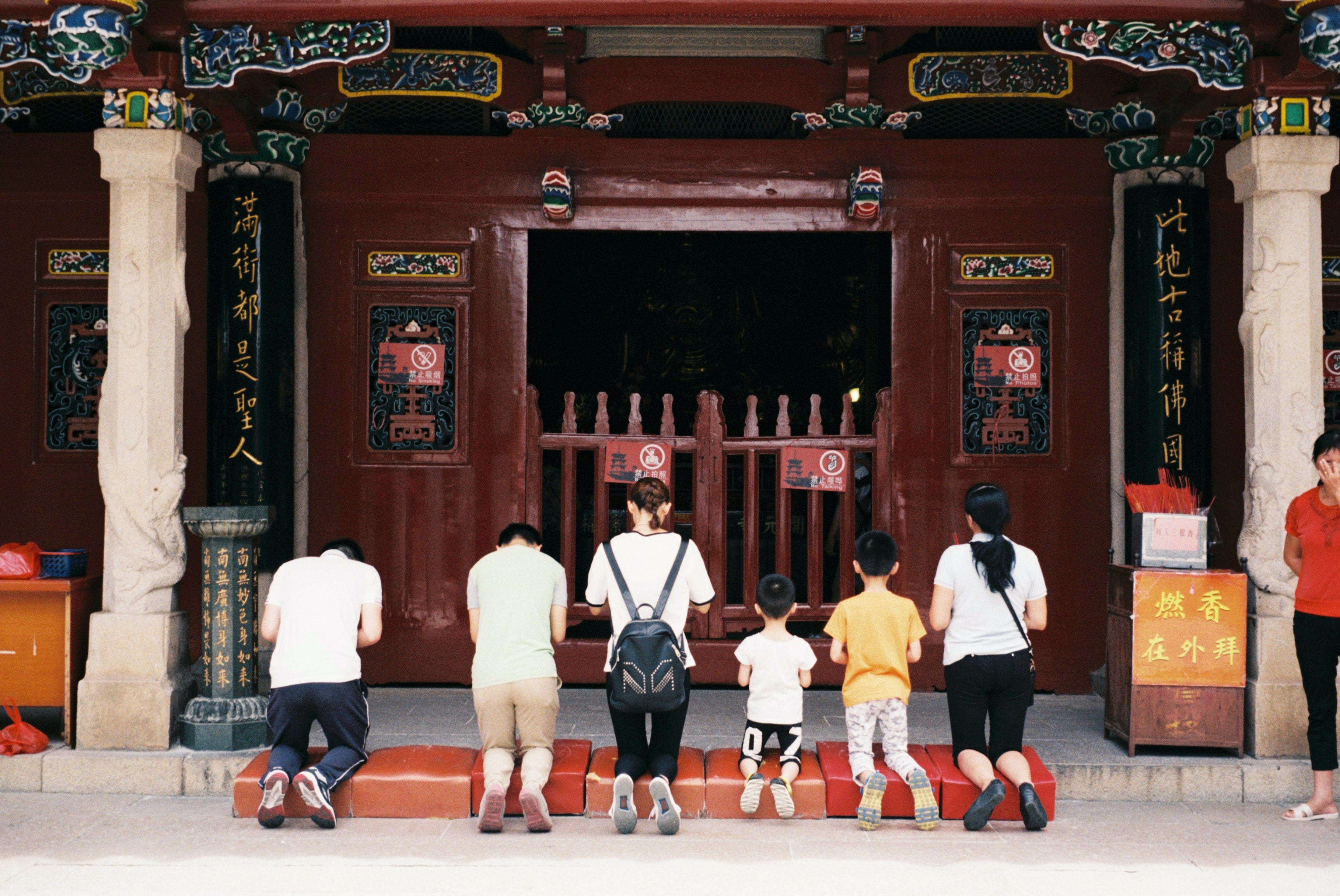 A family praying at an Asian temple