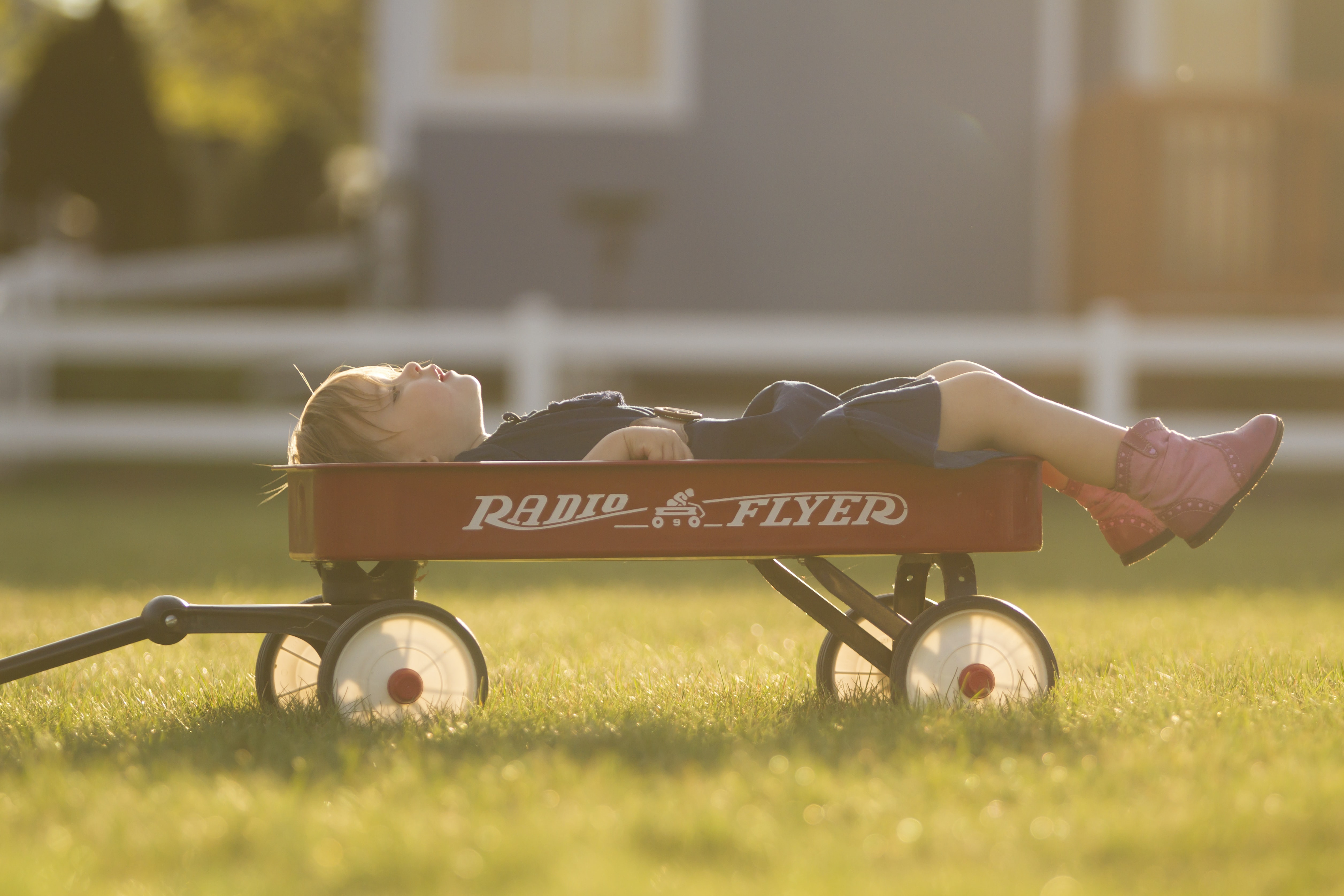 A little boy laying on top of a red wagon on the grass
