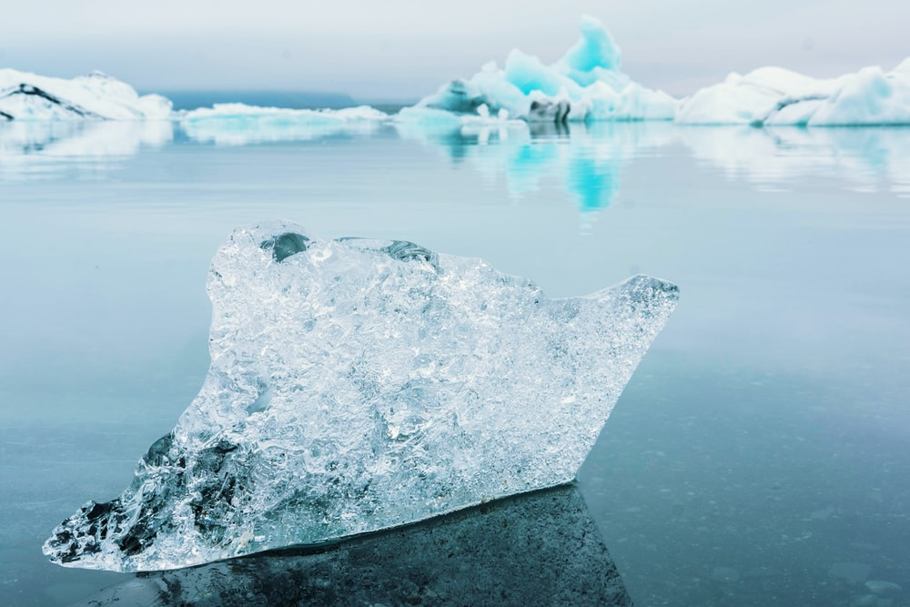 clear iceberg on blue ocean water
