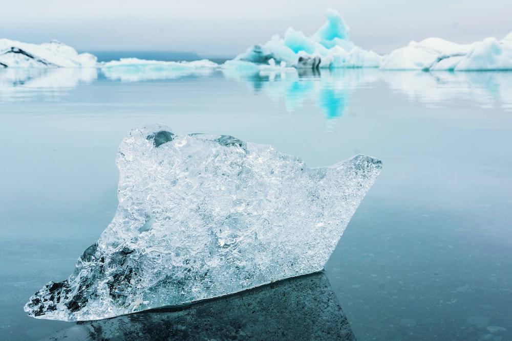 clear iceberg on blue ocean water