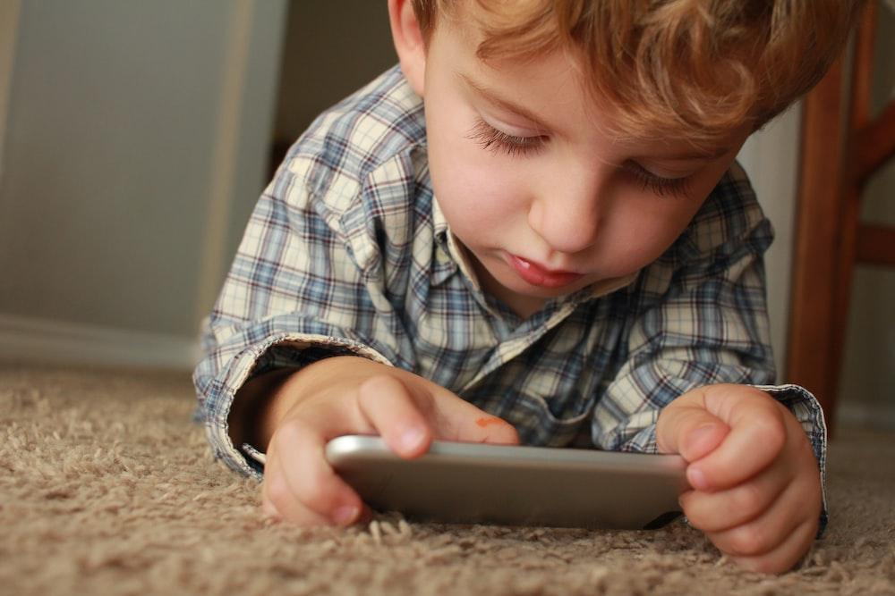 boy holding smartphone while lying on rug