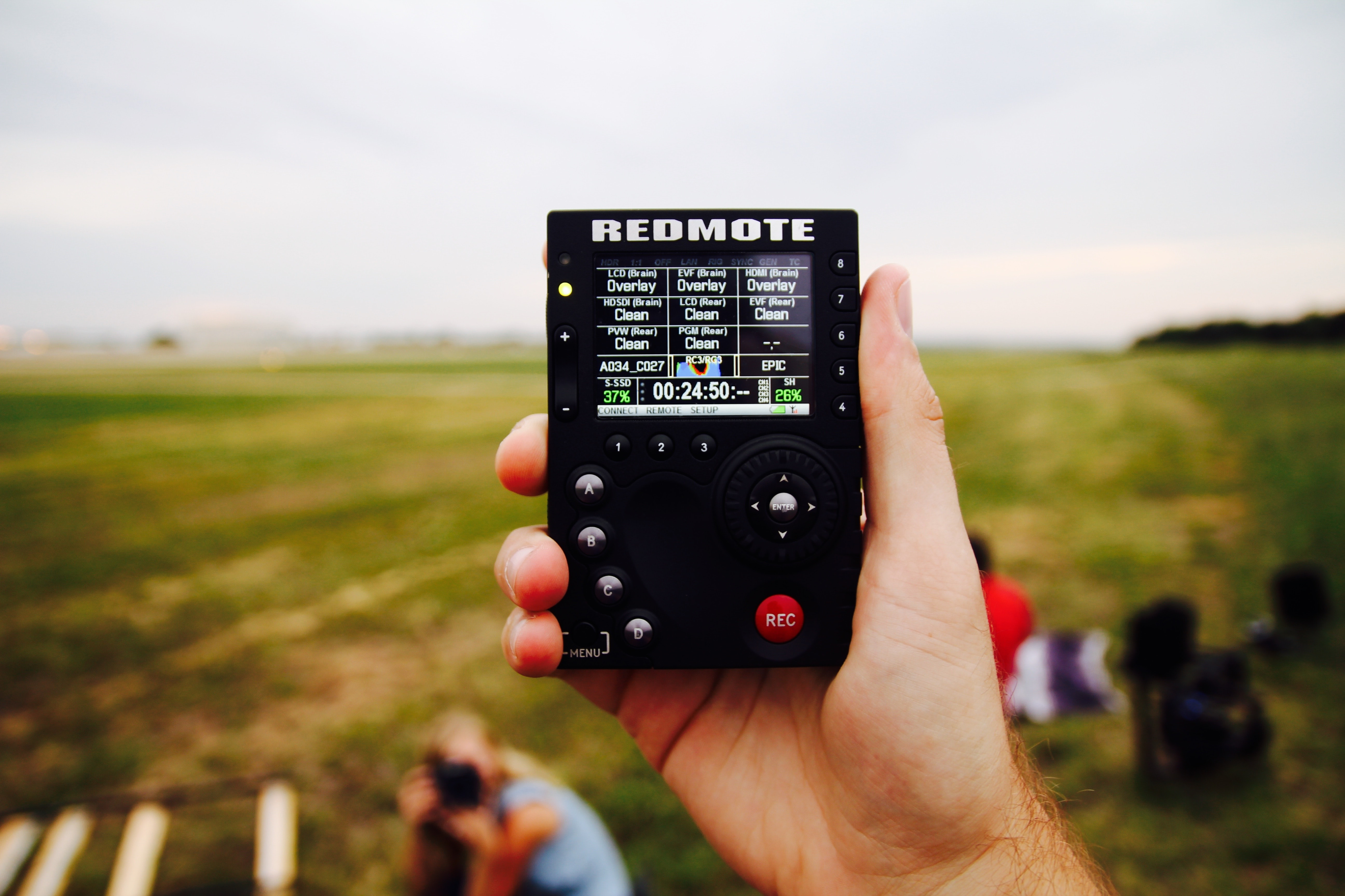 Hand holding black Redmote remote with record button in front of a field