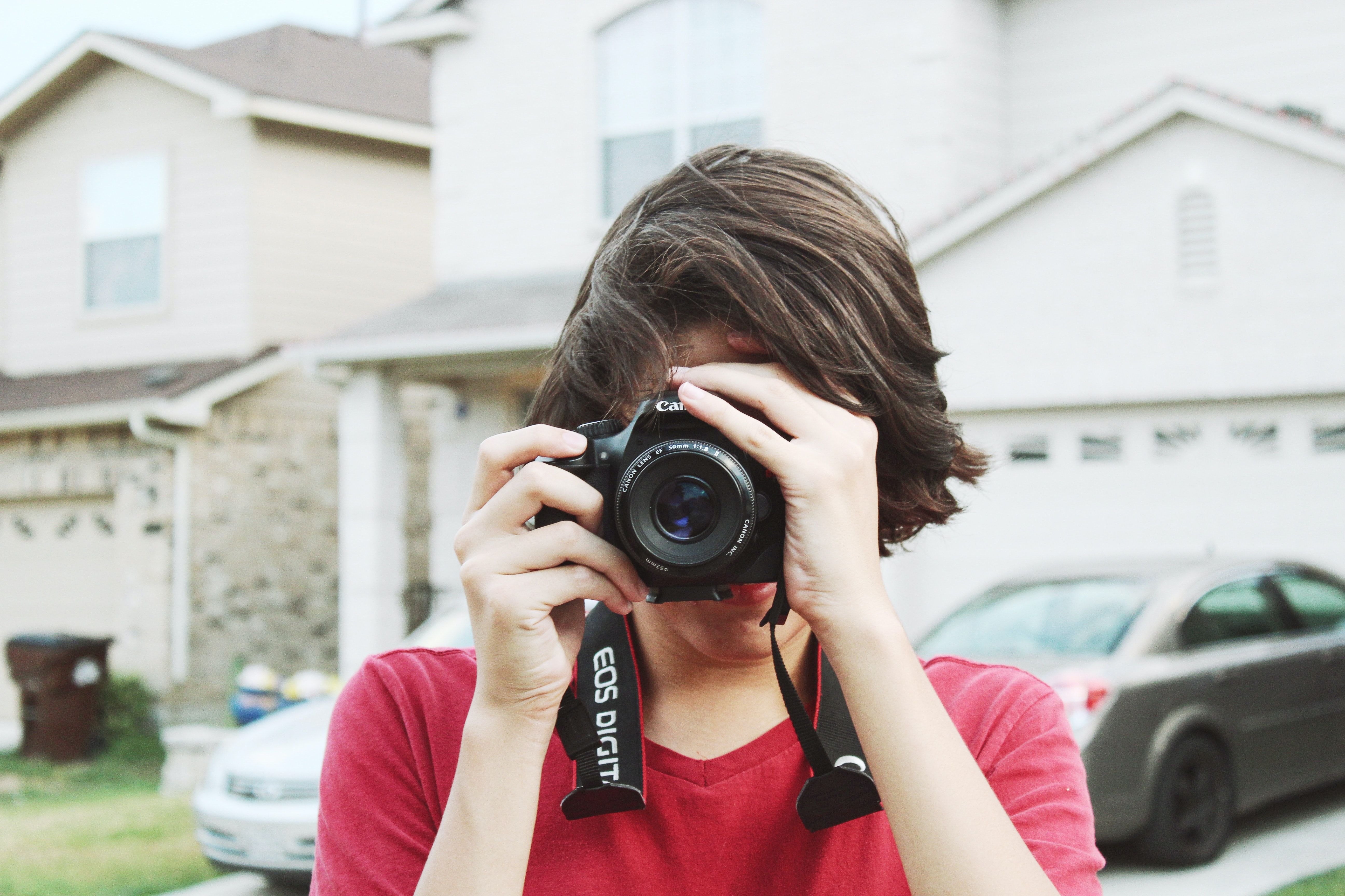 A guy wearing a red t-shirt taking a photo with a Canon camera