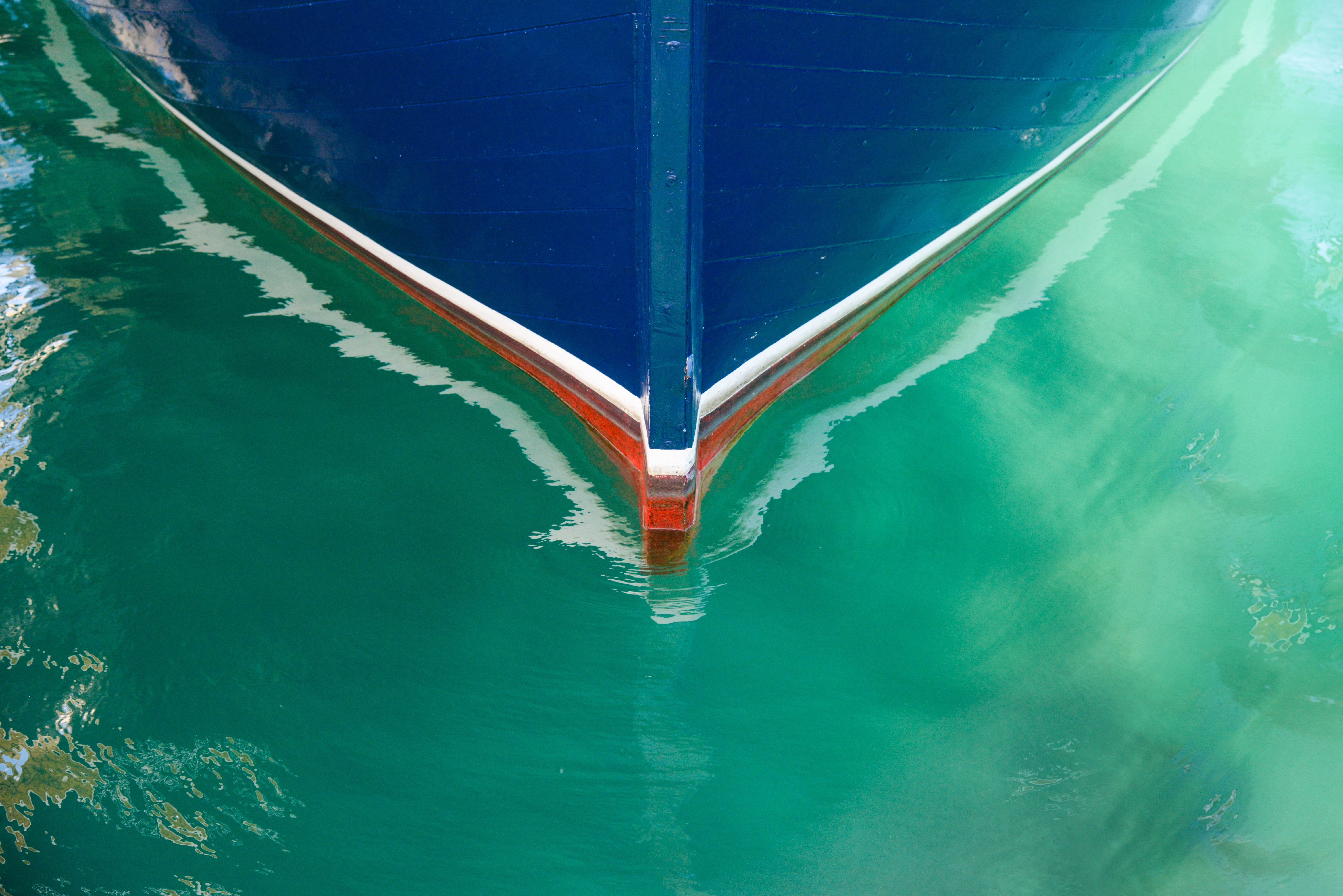 Stern of a blue boat rides through clear waters