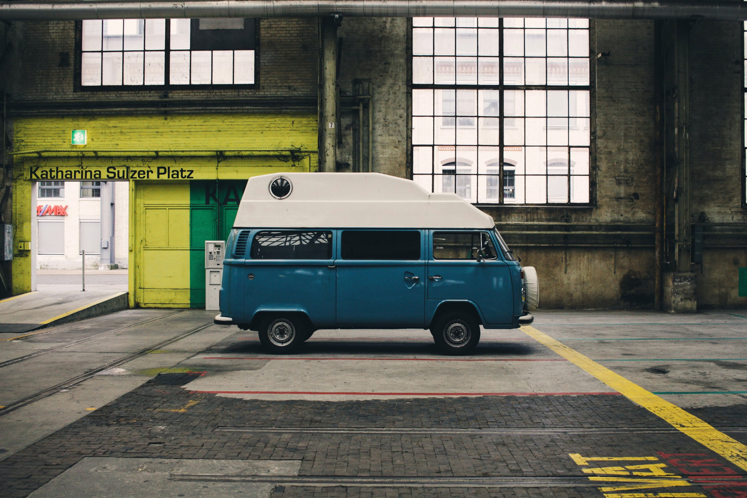 Green van in a dark brick garage labeled Katharina Sulzer Platz
