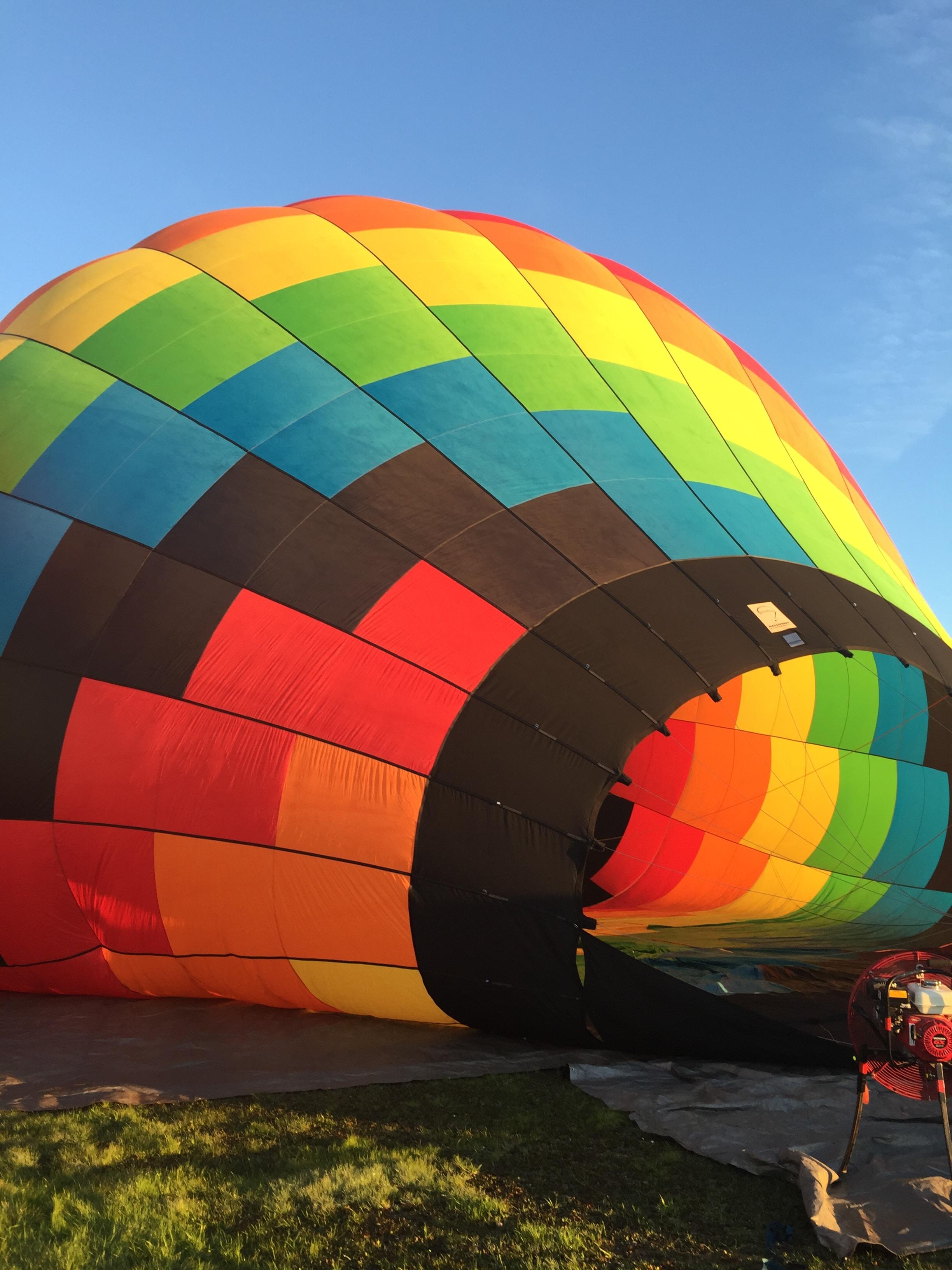 blue, green, and orange hot air balloon on grass field