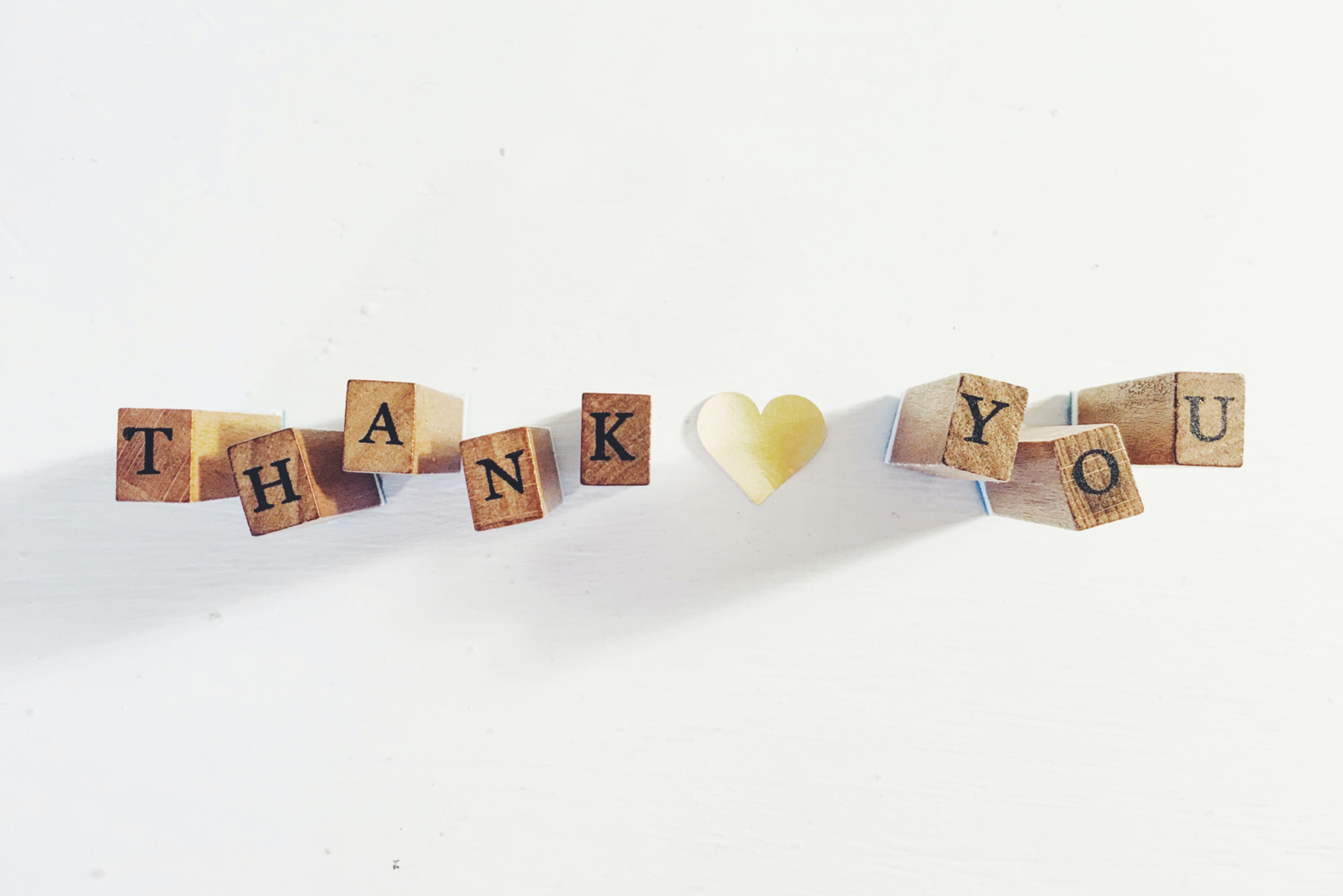 "A set of wooden lettered cubes arranged to spell ""THANK YOU"" with a heart in between"