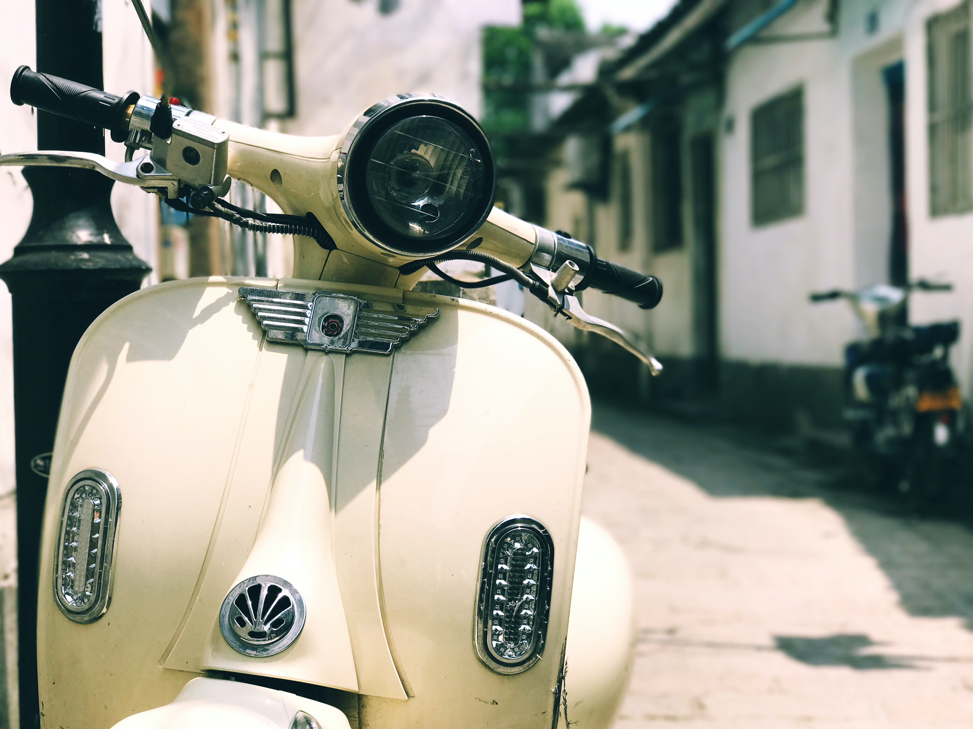 A white vintage scooter in a rural alley