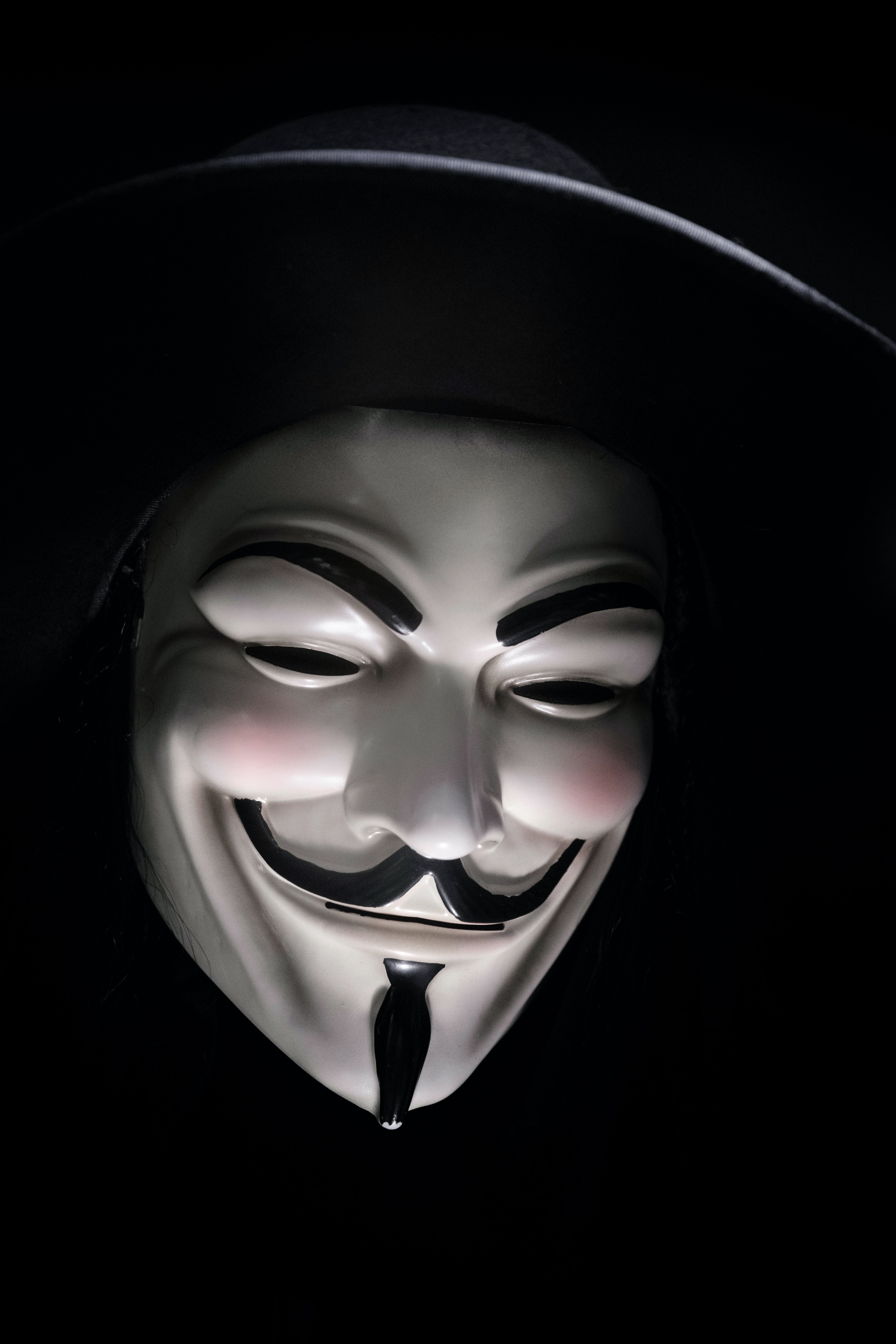 A smiling Guy Fawkes mask in shadow against a black background
