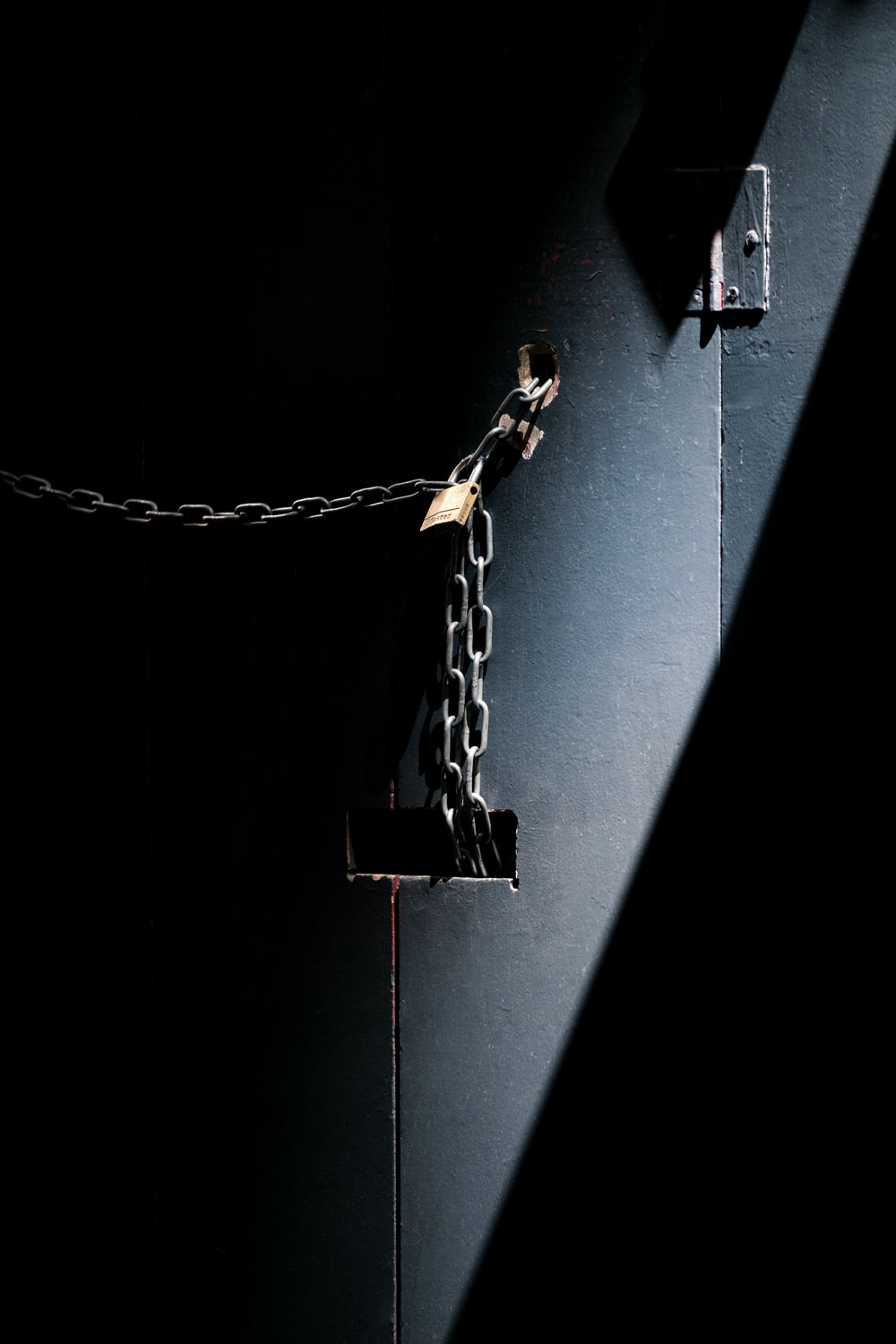 Rusty chain and a padlock close up a door in the shadows
