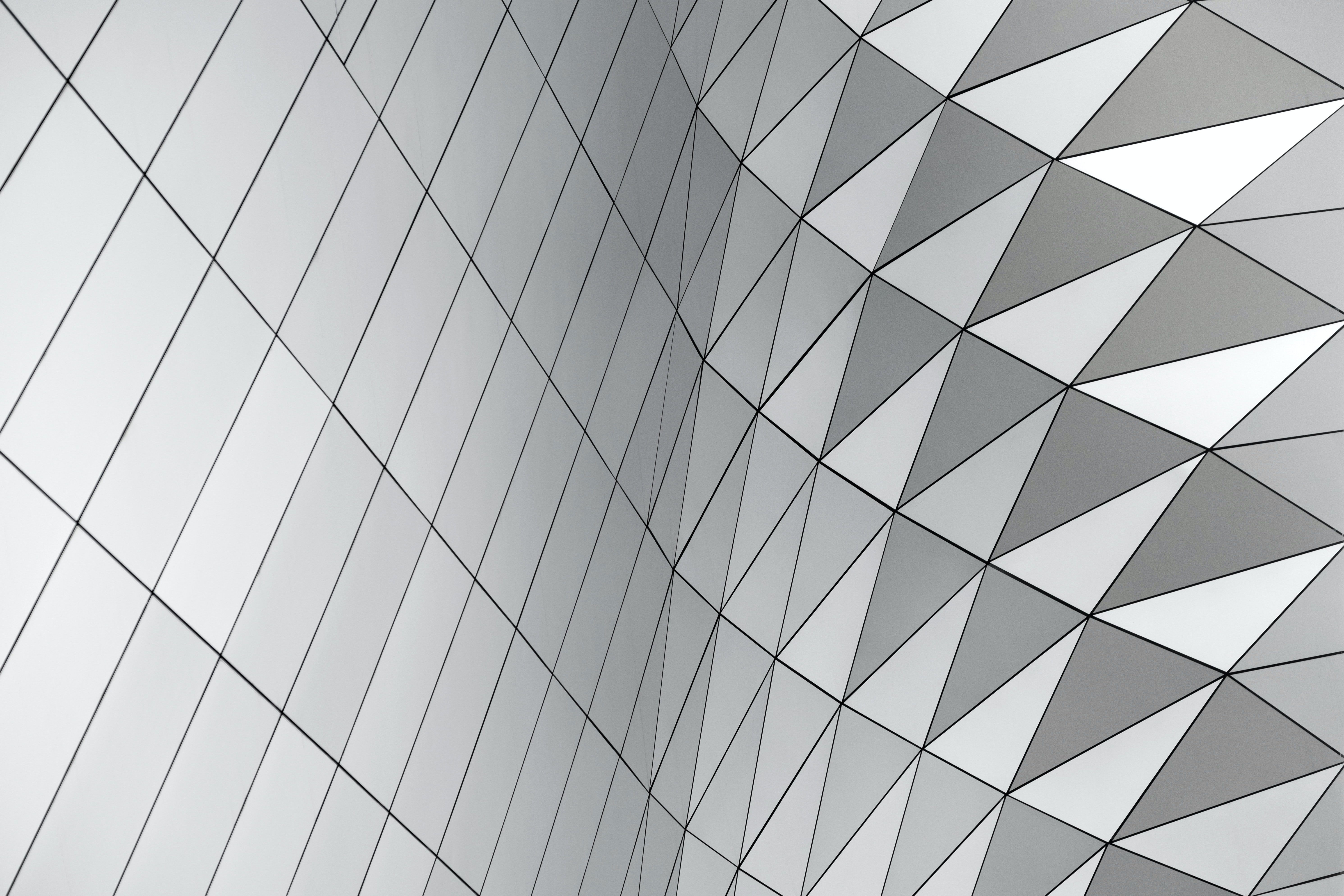 A pattern with squares and triangles in a curving gray facade