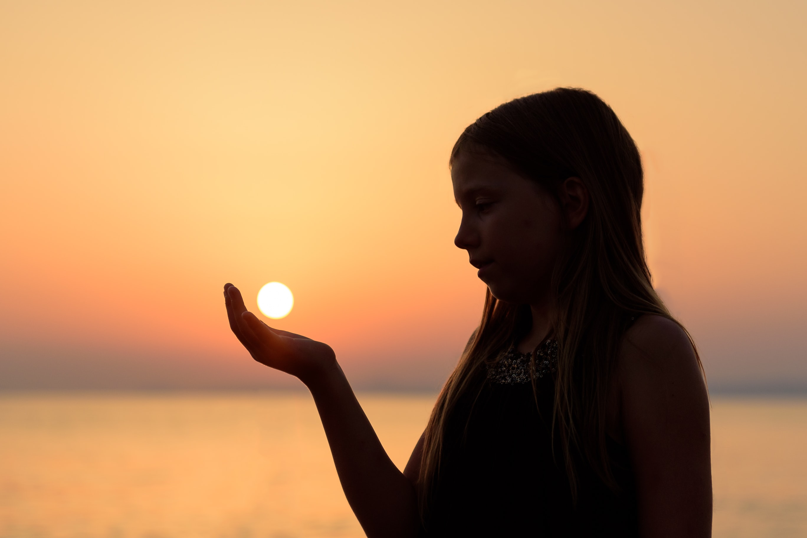 A woman in silhouette appears to hold the setting sun in her hand in Koundouros