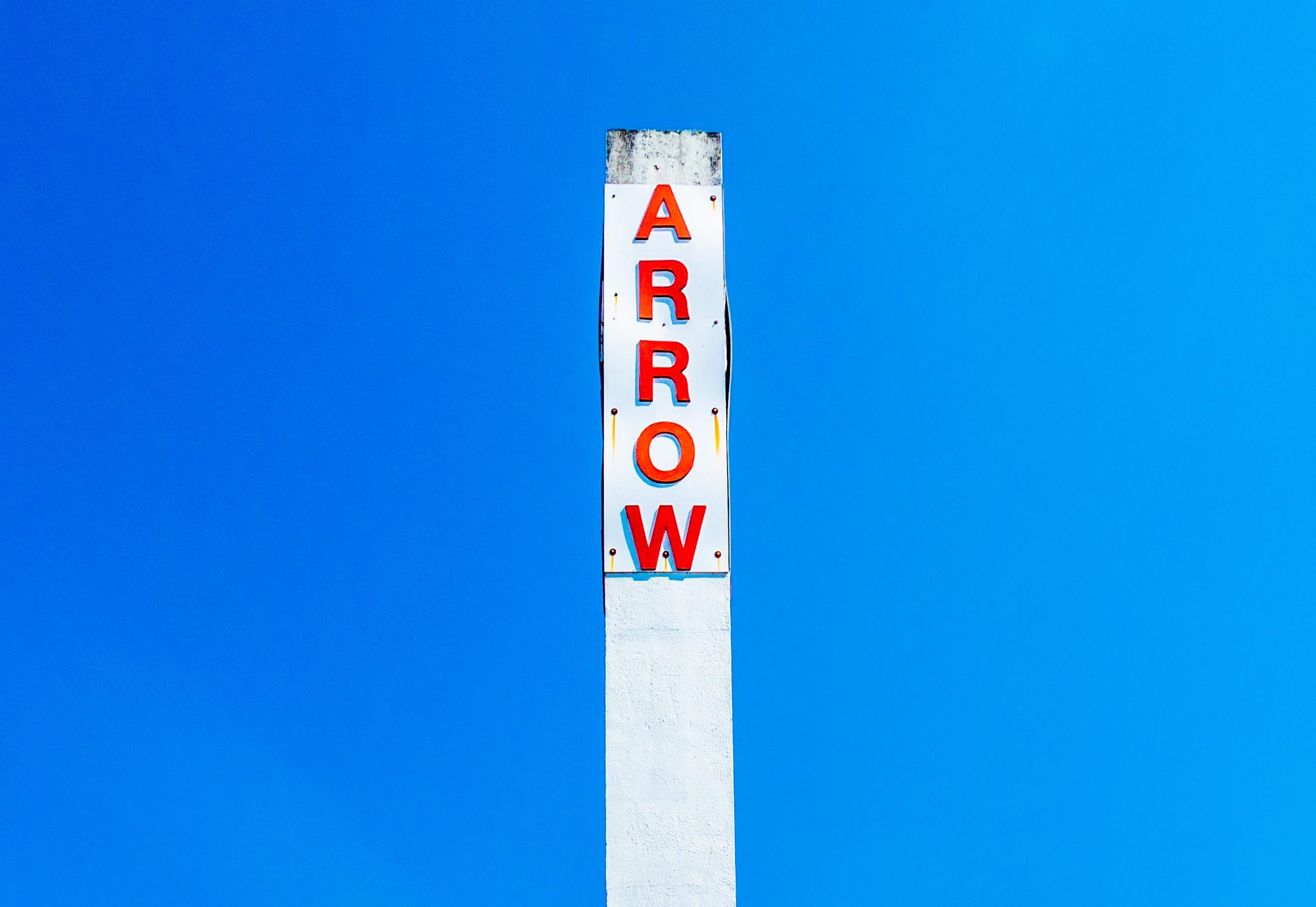 Arrow signage under blue sky