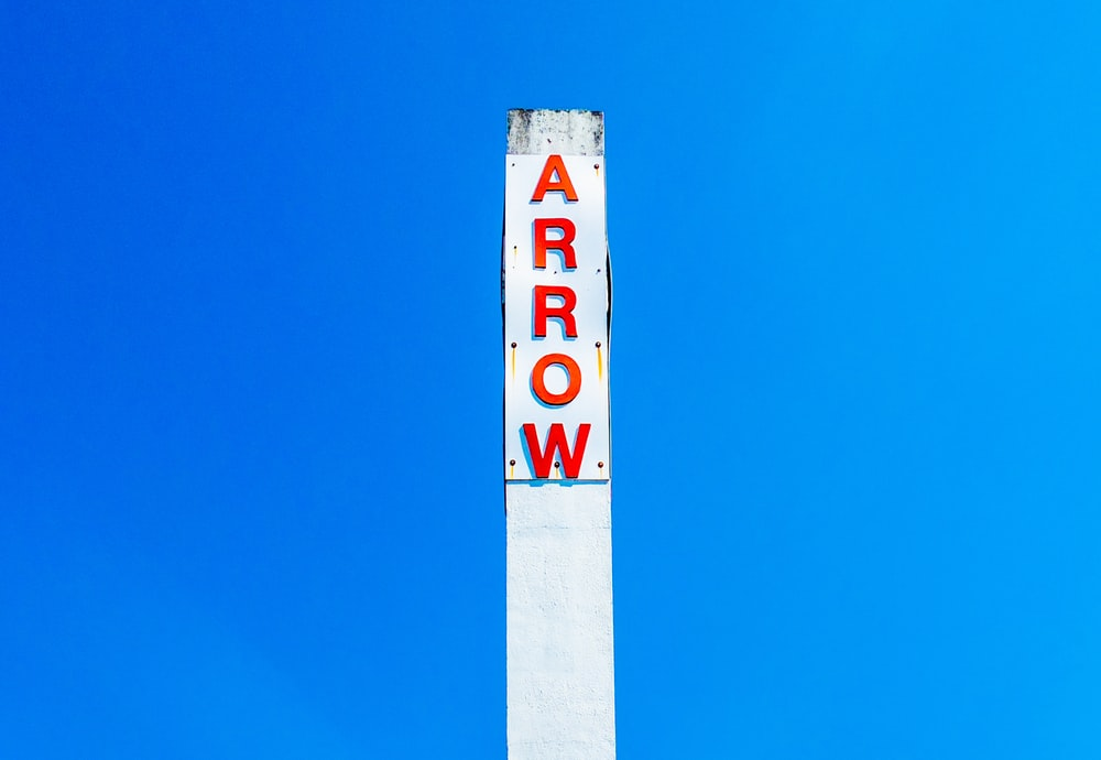 Arrow signage under blue sky