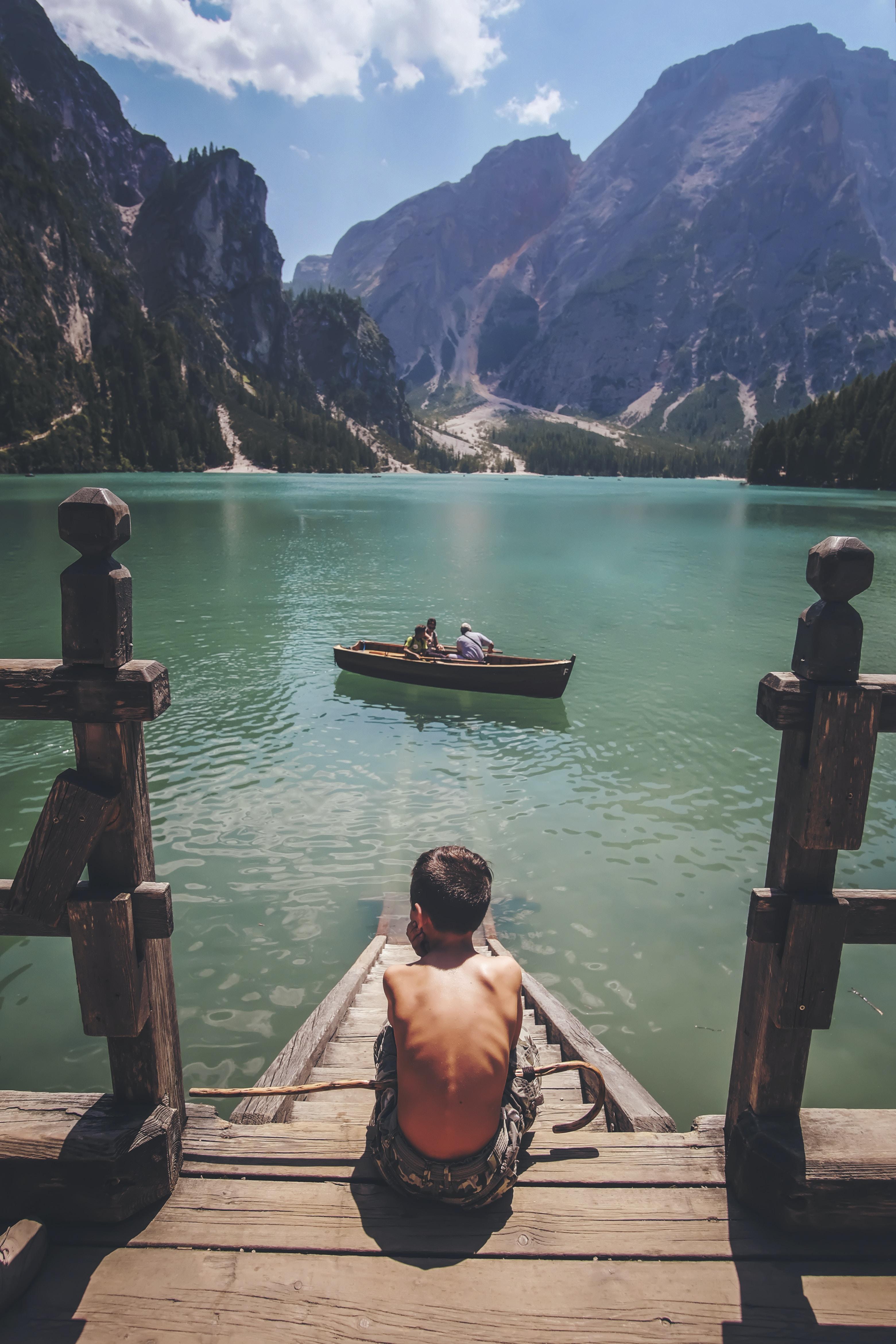 boy sitting on dock during daytime