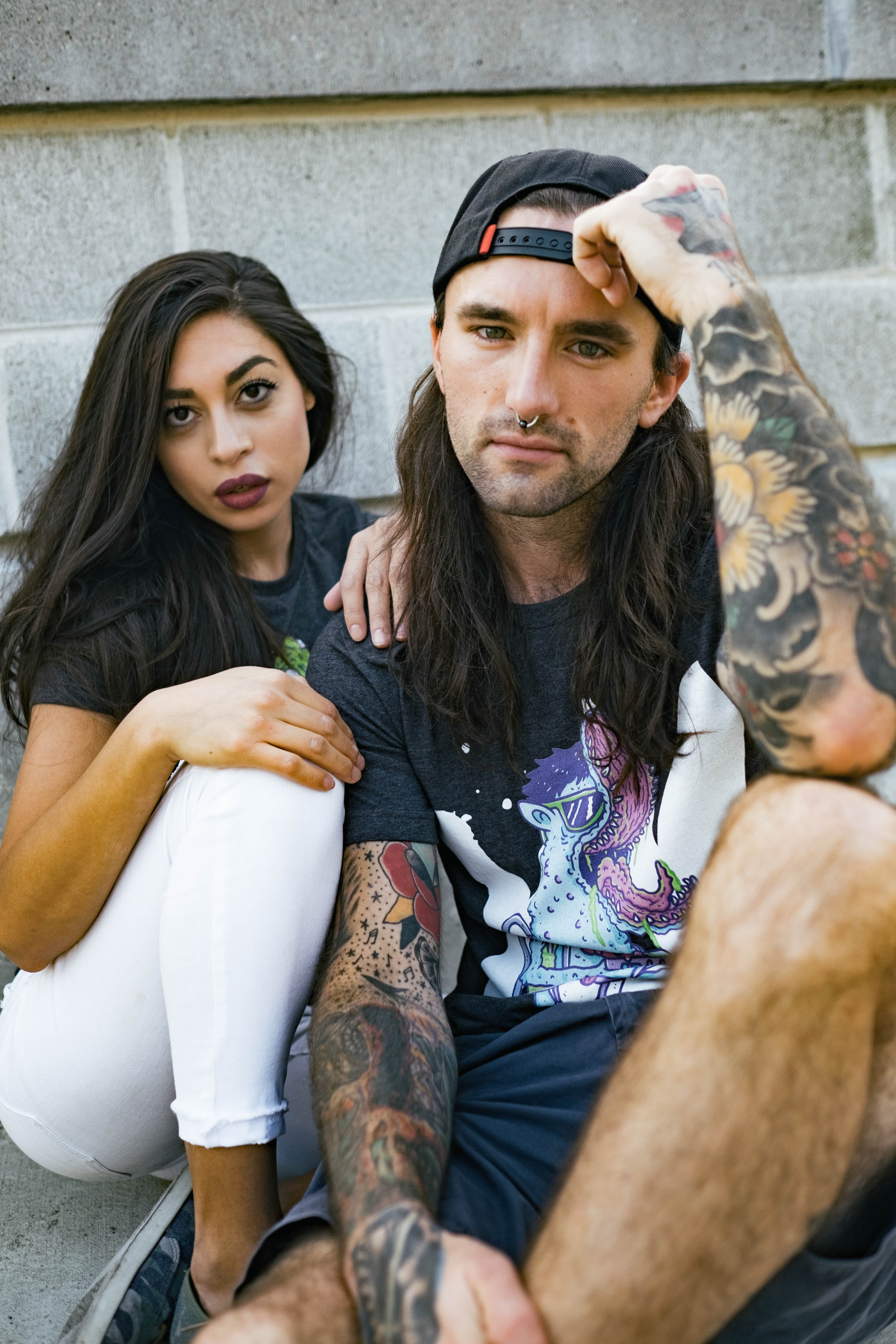 man and woman sitting against concrete wall