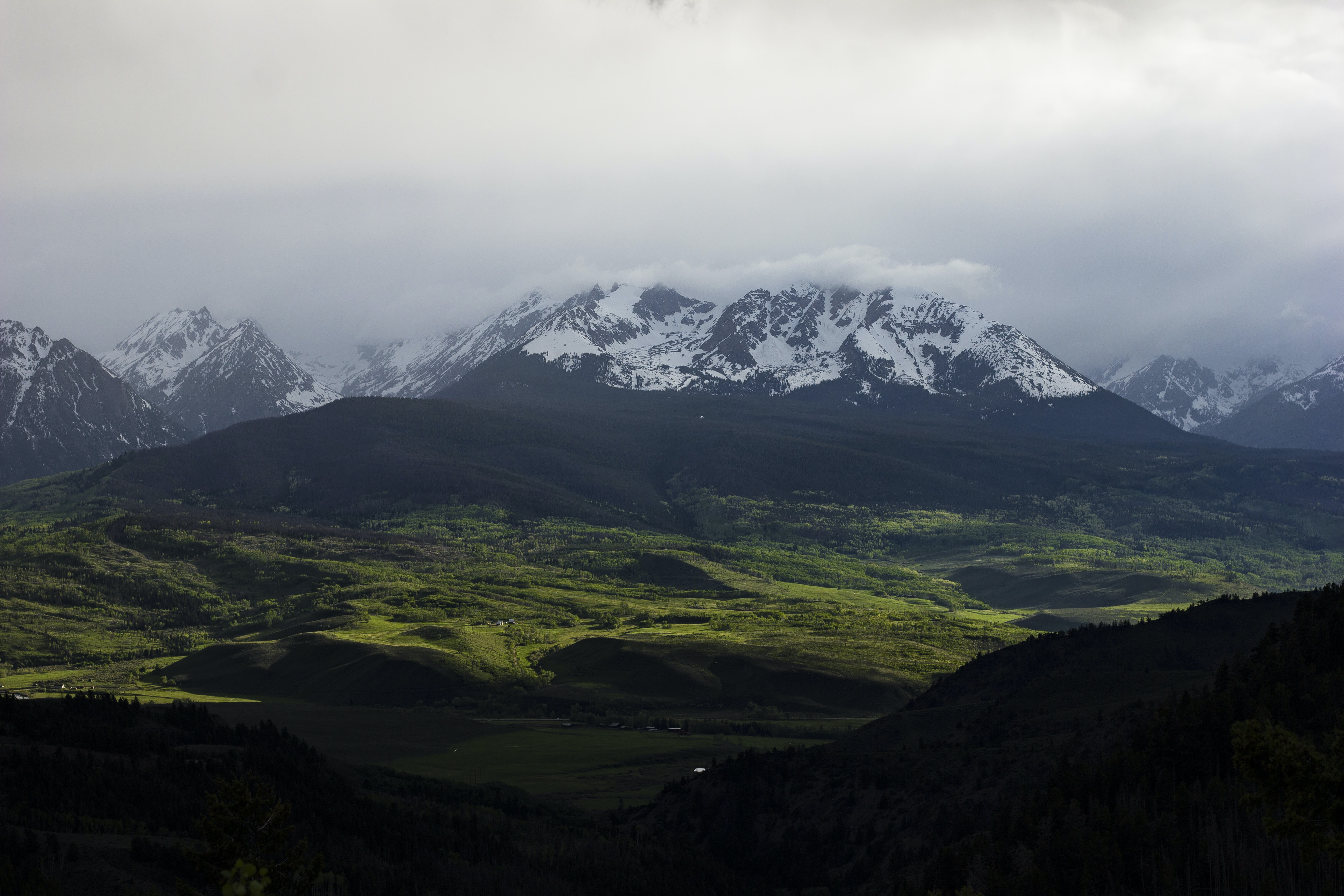 panoramic photo of glacier mountain above forest