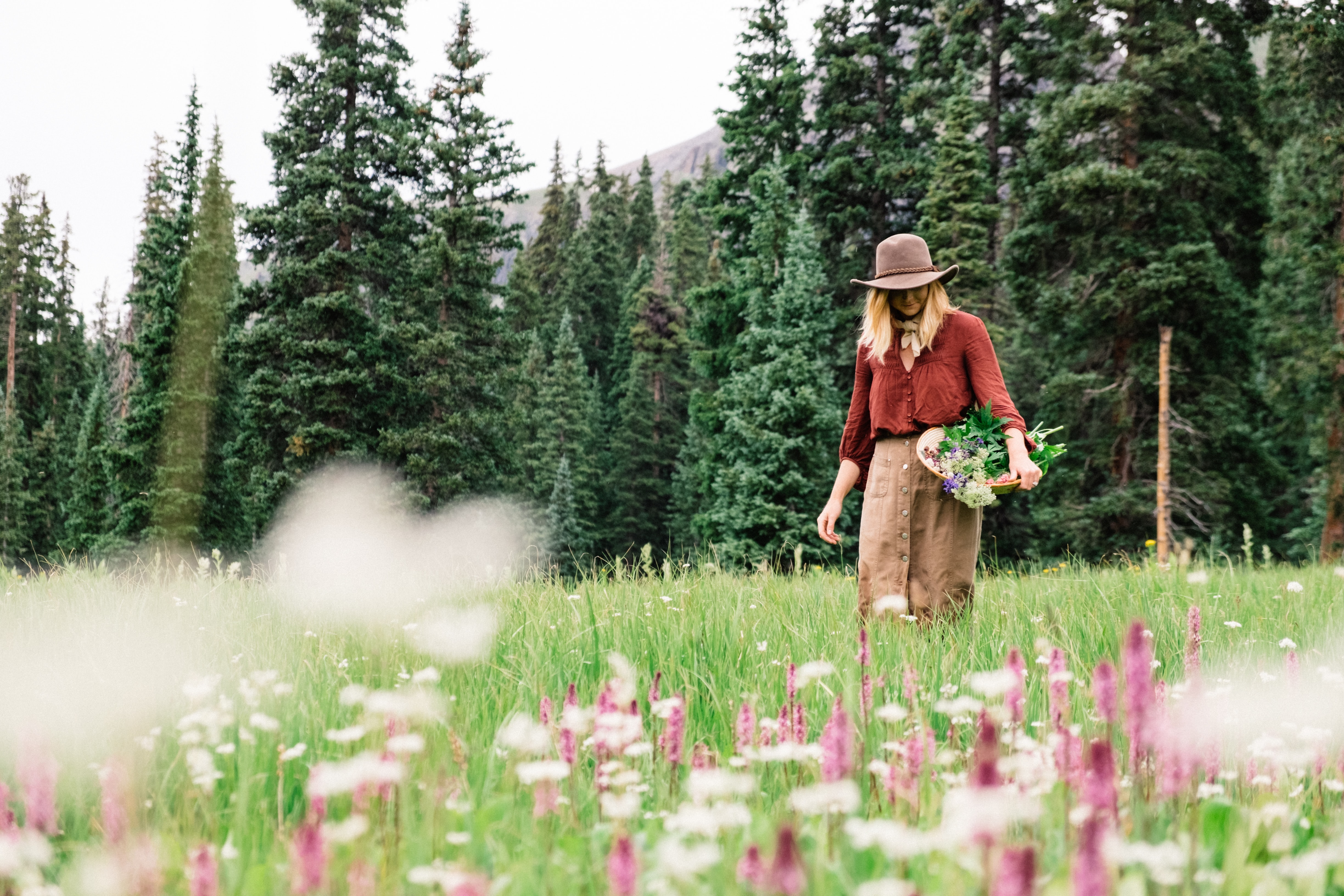 A woman in a hat walks through a meadow, holding a basket of flowers
