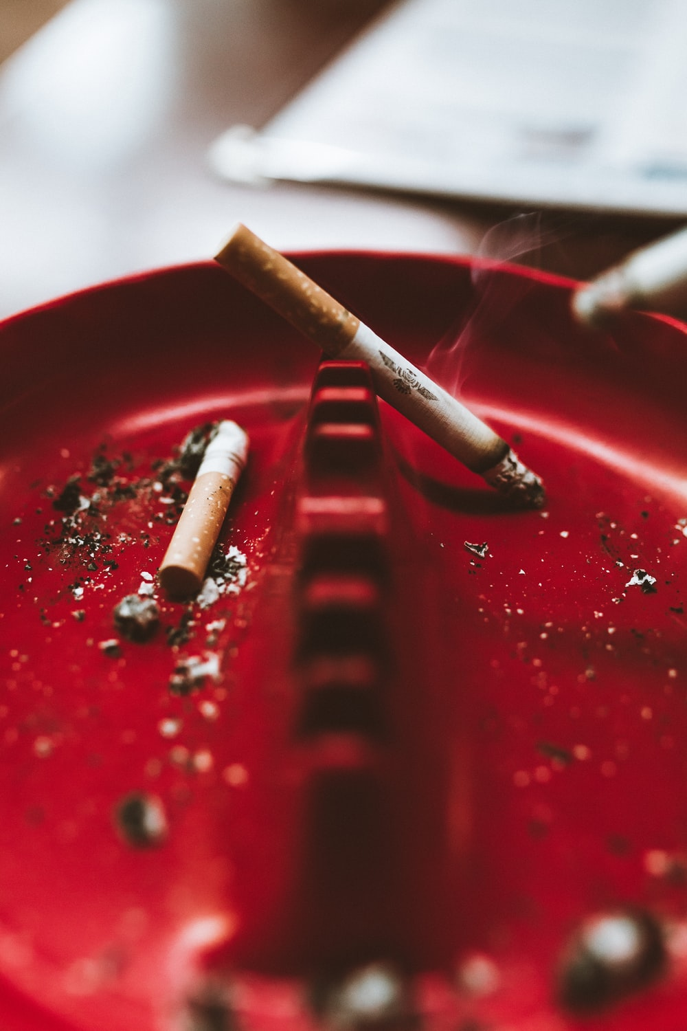 shallow focus photo of white cigarette stick on red ashtray