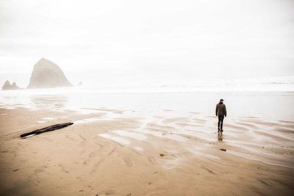 man walking on shore during daytime