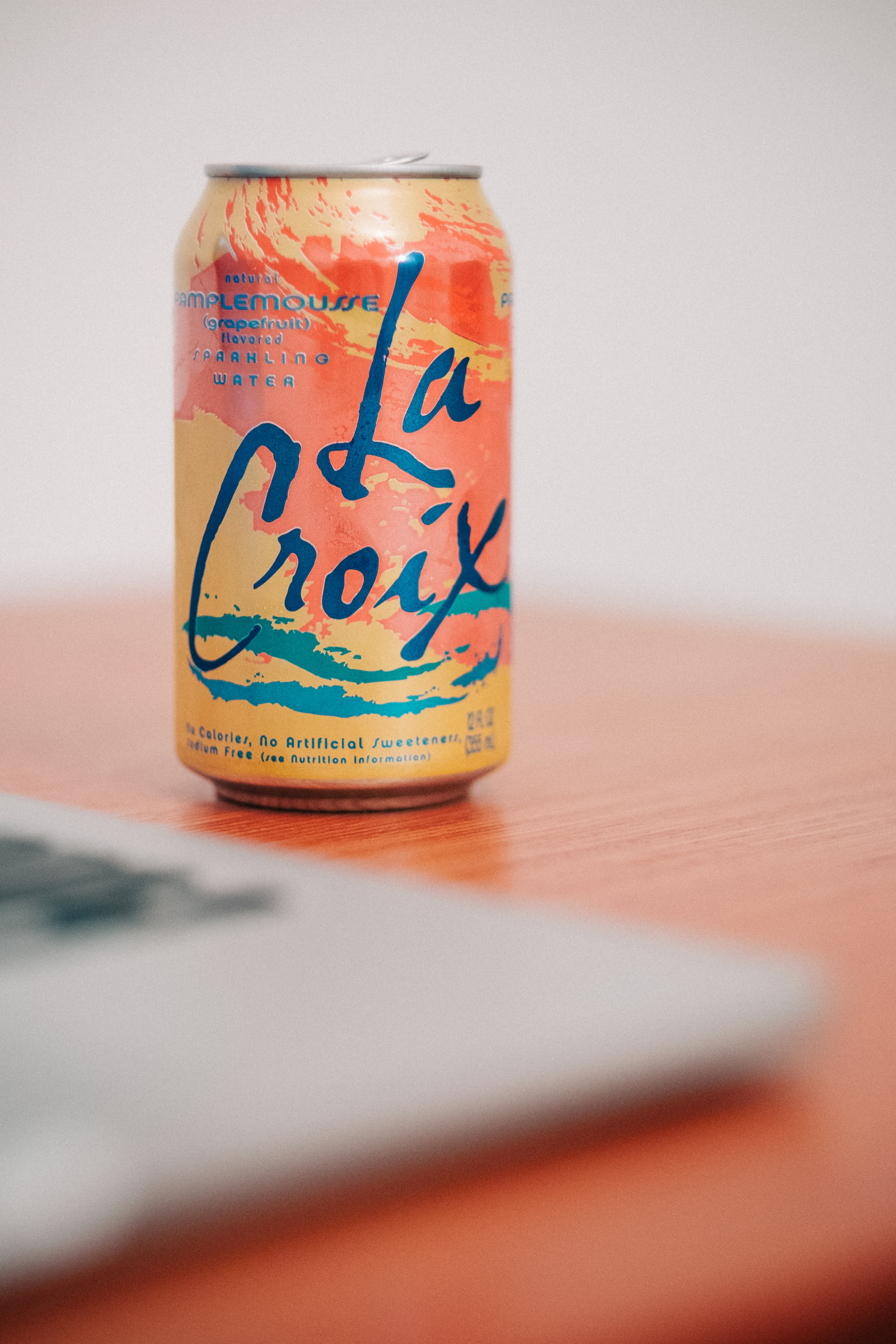 Orange La Croix on a table in brightly lit room
