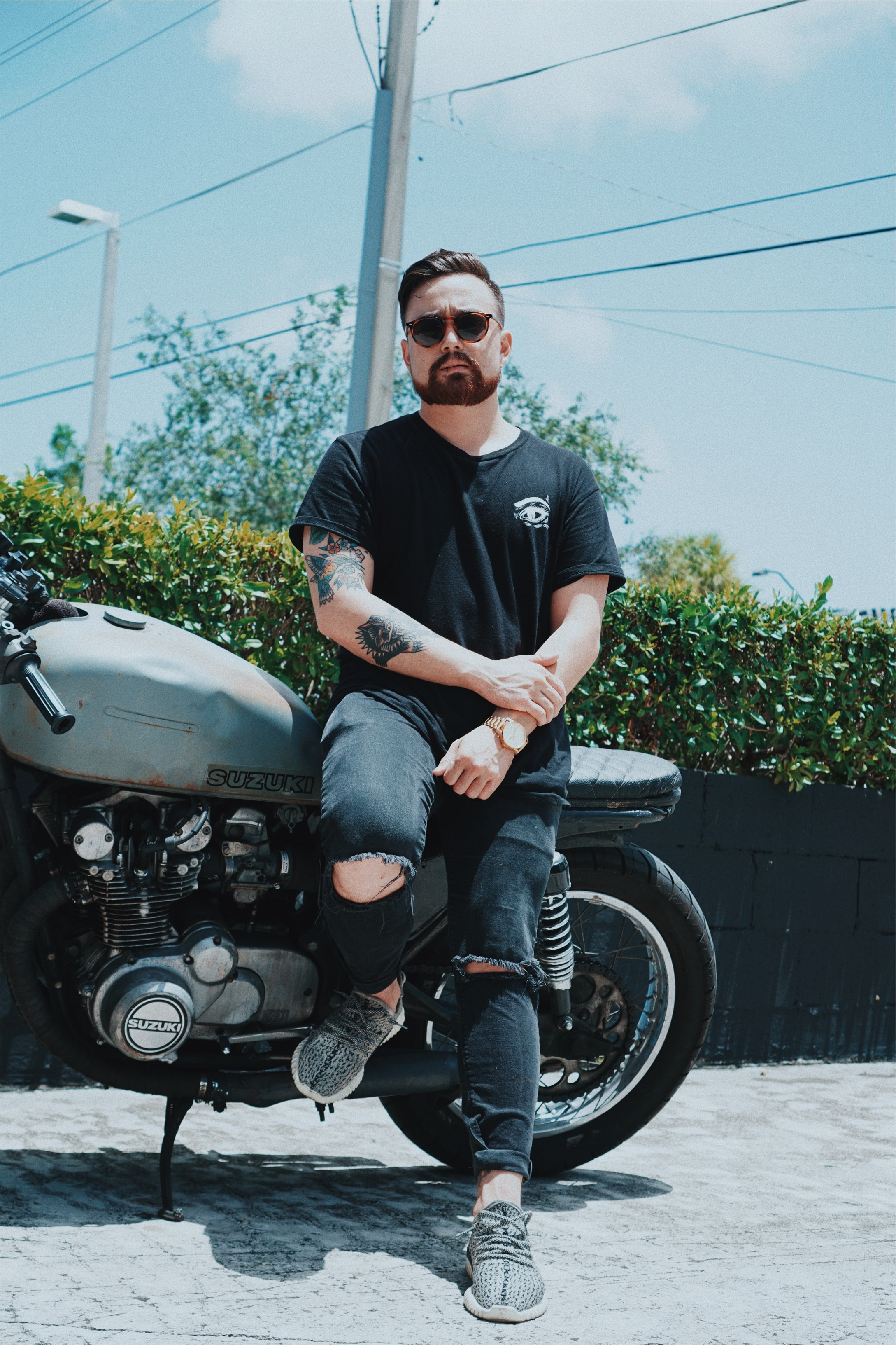 Tattooed man with a beard and shades in a black shirt, distressed jeans and sneakers leaning on his Suzuki motorcycle in front of bushes and telephone poles