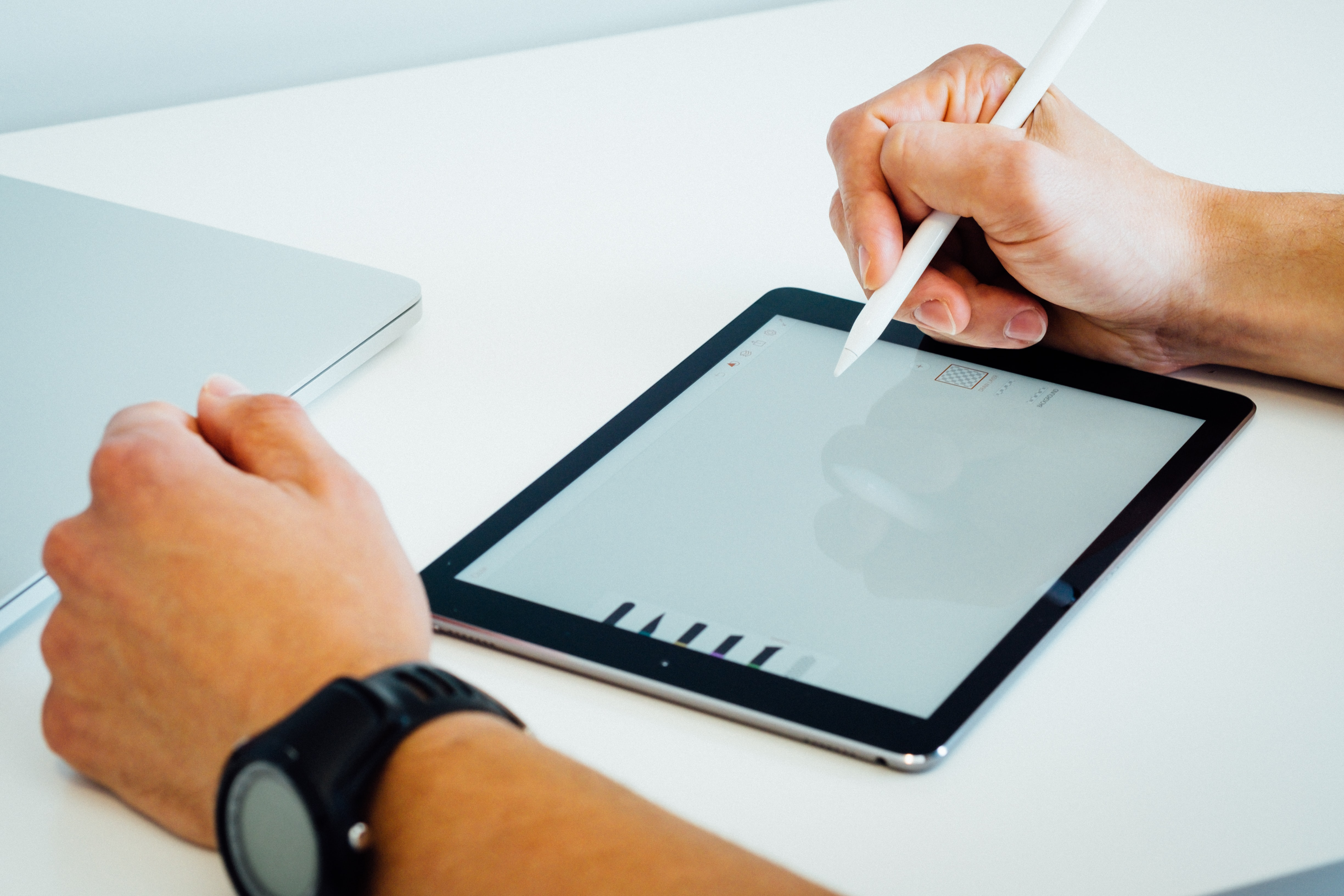 A man drawing on an iPad with a stylus