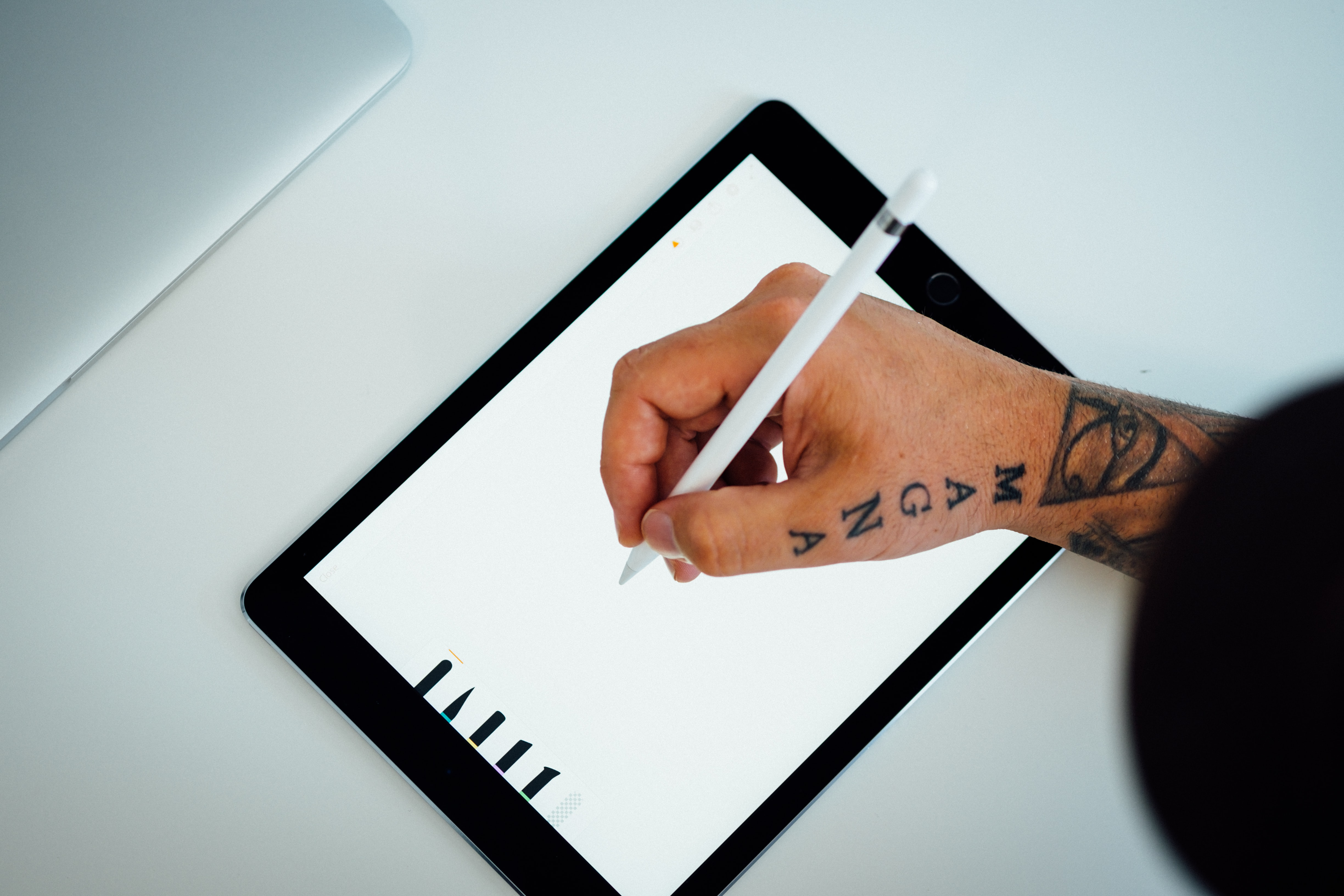 Hand of an artist with a tattoo drawing on an iPad