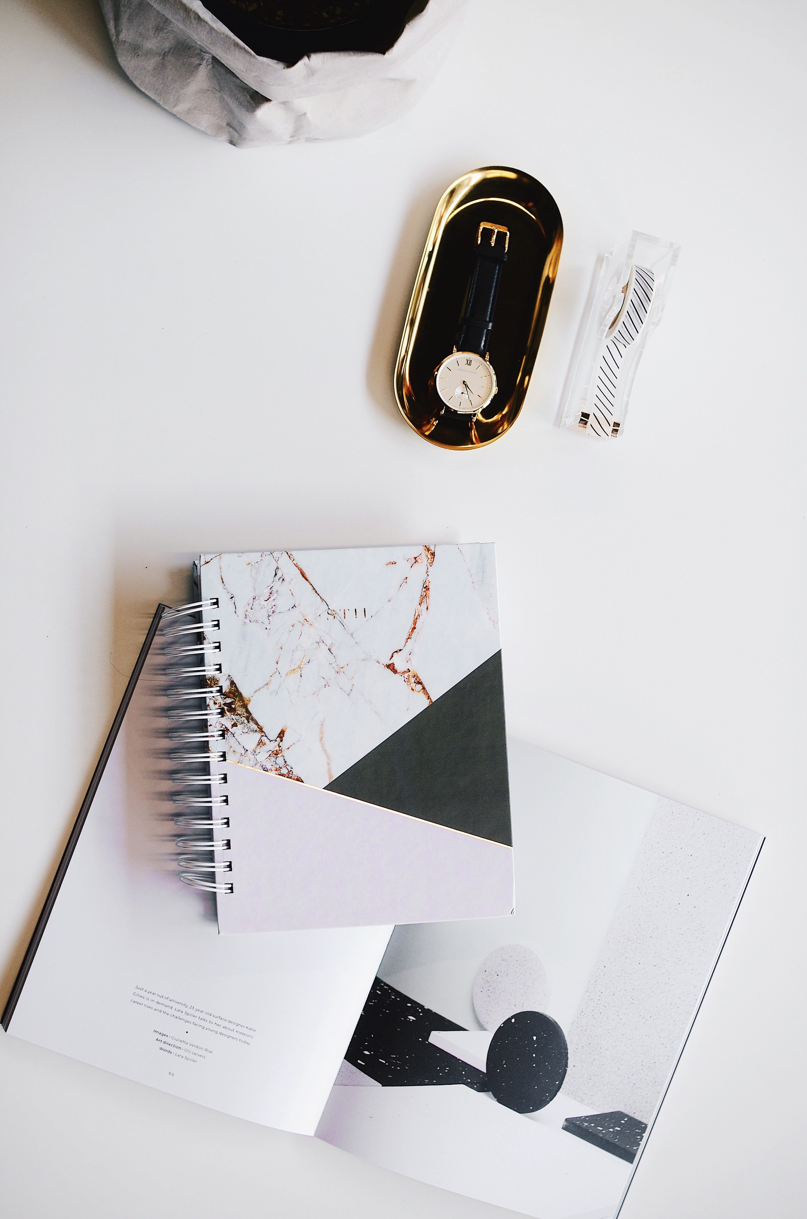 A flatlay of a watch, book, planner, and tape dispenser on a table