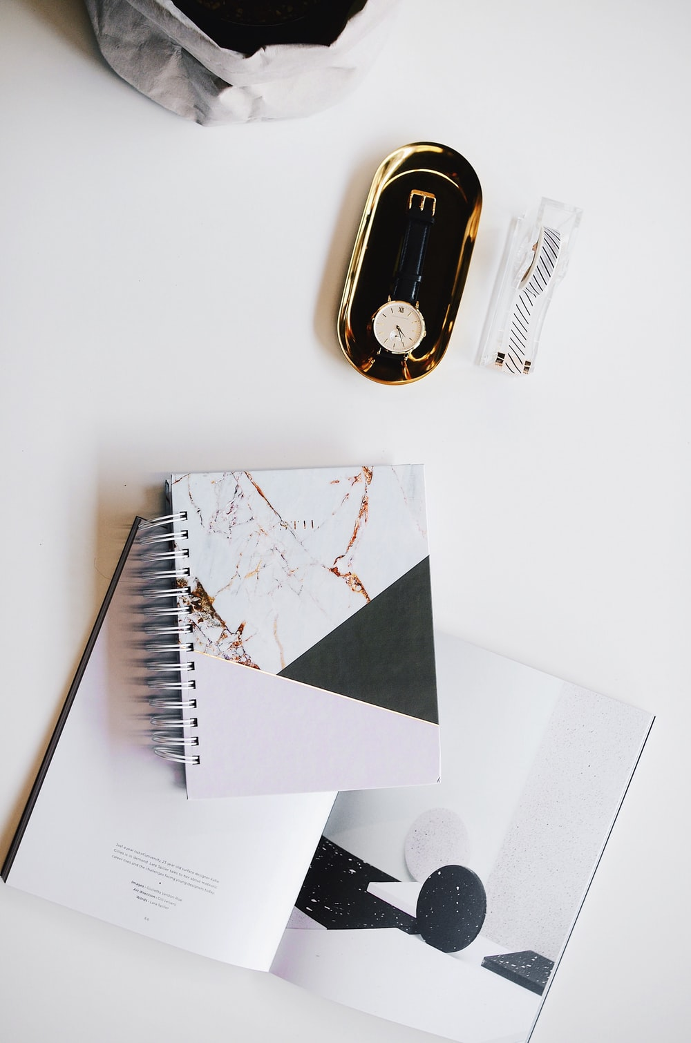 top view photography of round silver-colored analog watch with black leather strap on case near white covered notebook