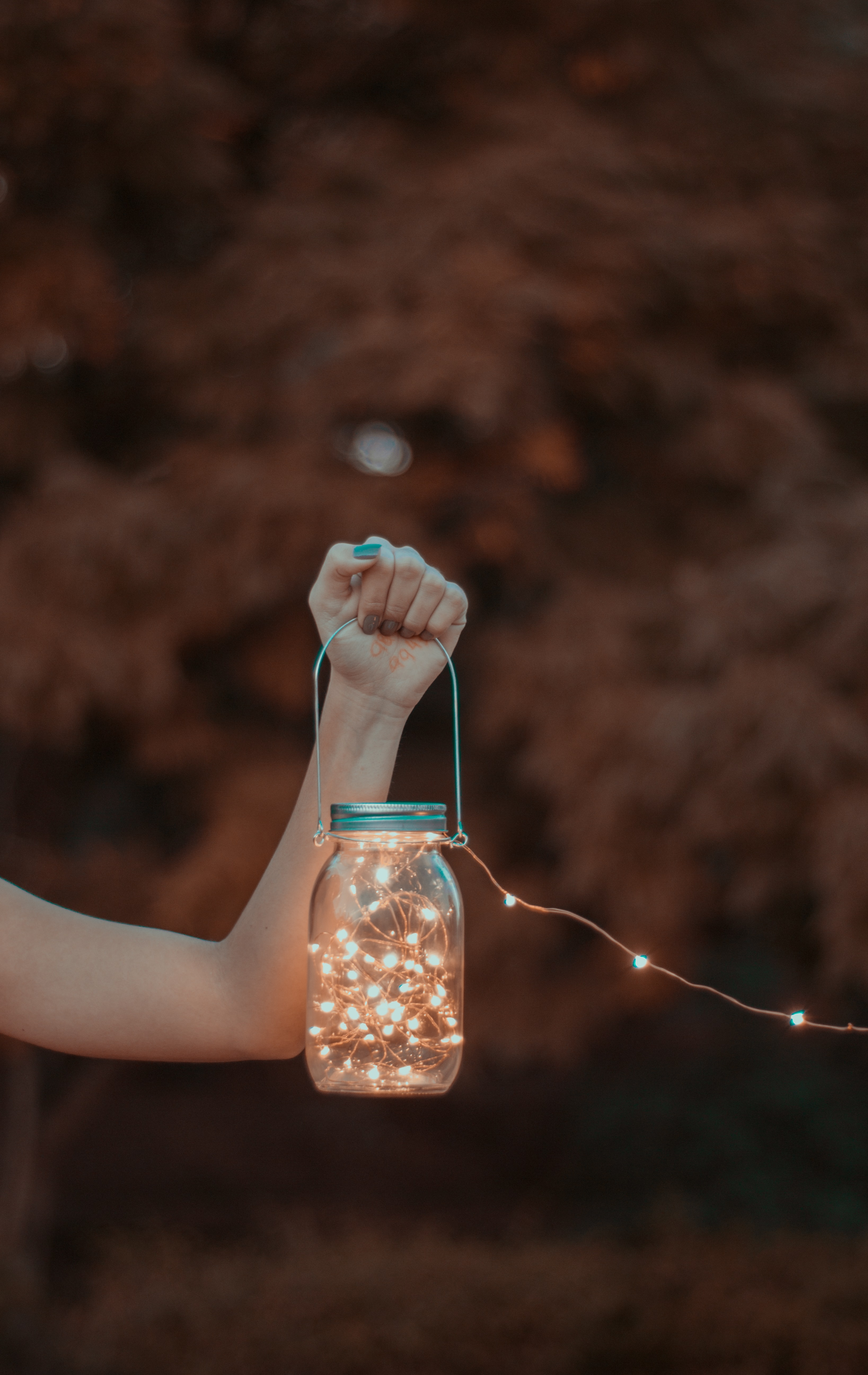 person holding mason jar with string lights
