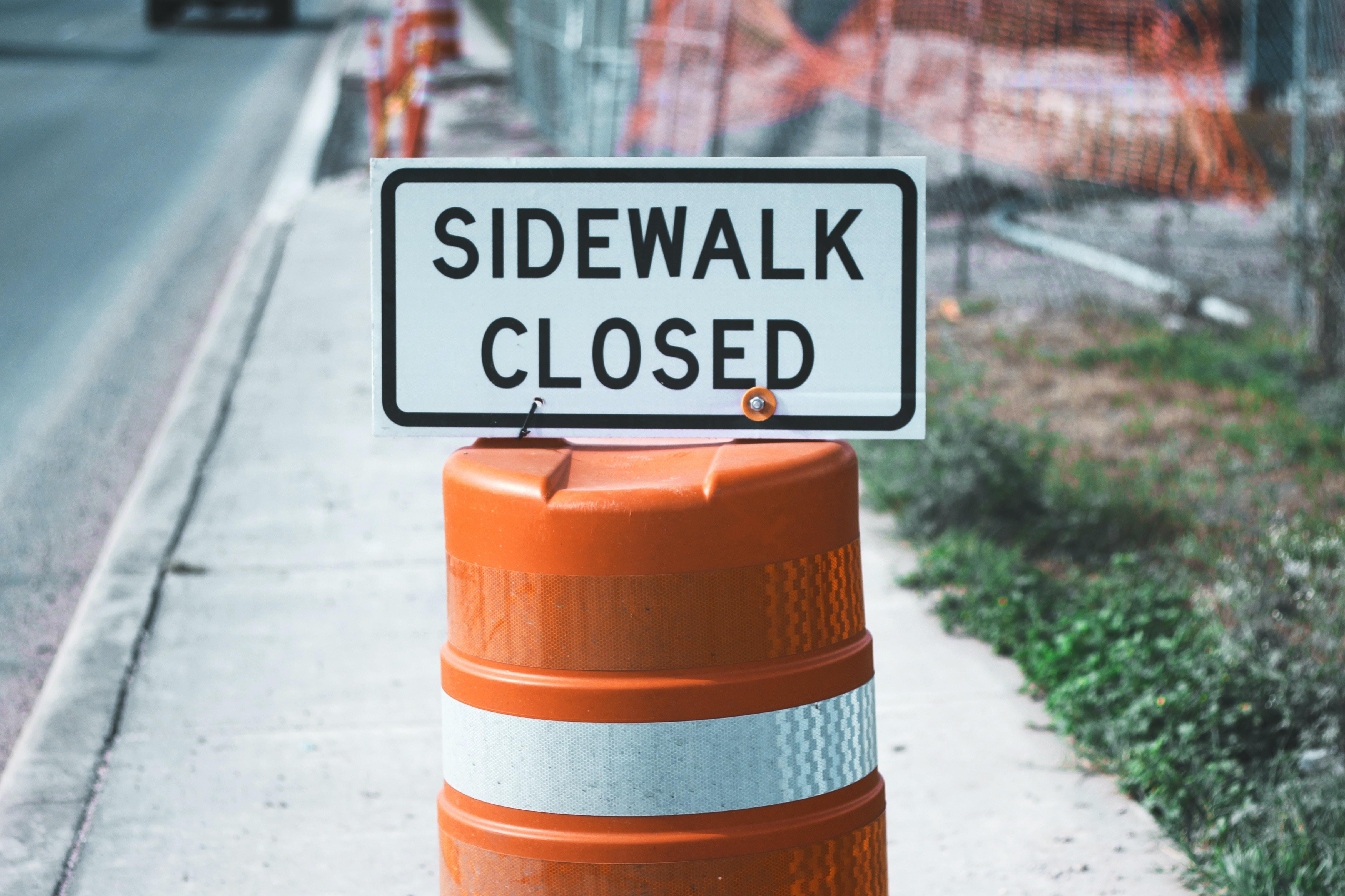 """A """"sidewalk closed"""" sign on an orange traffic cone"""