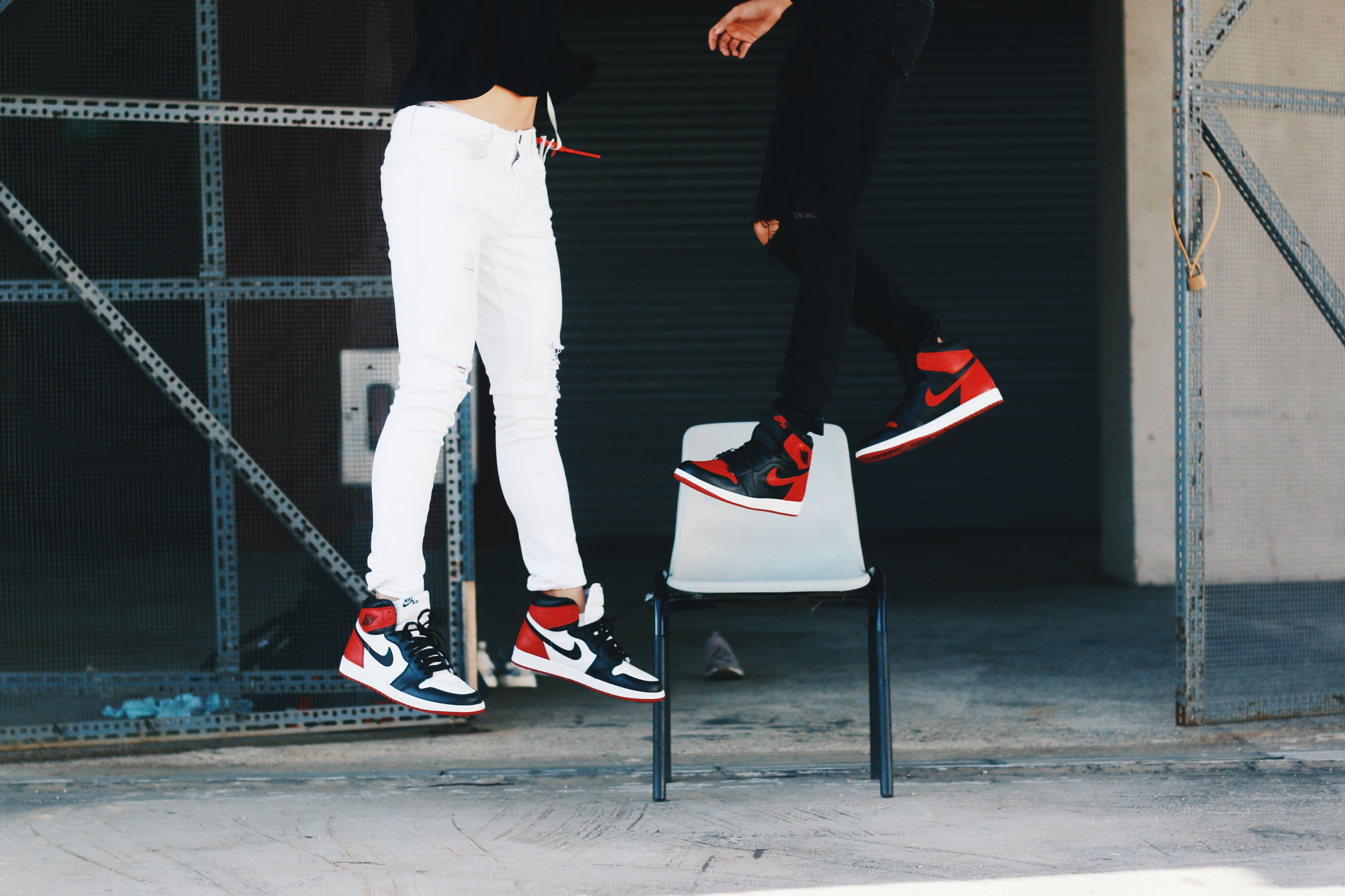 Two people are floating in mid-air wearing Nike sports shoes.